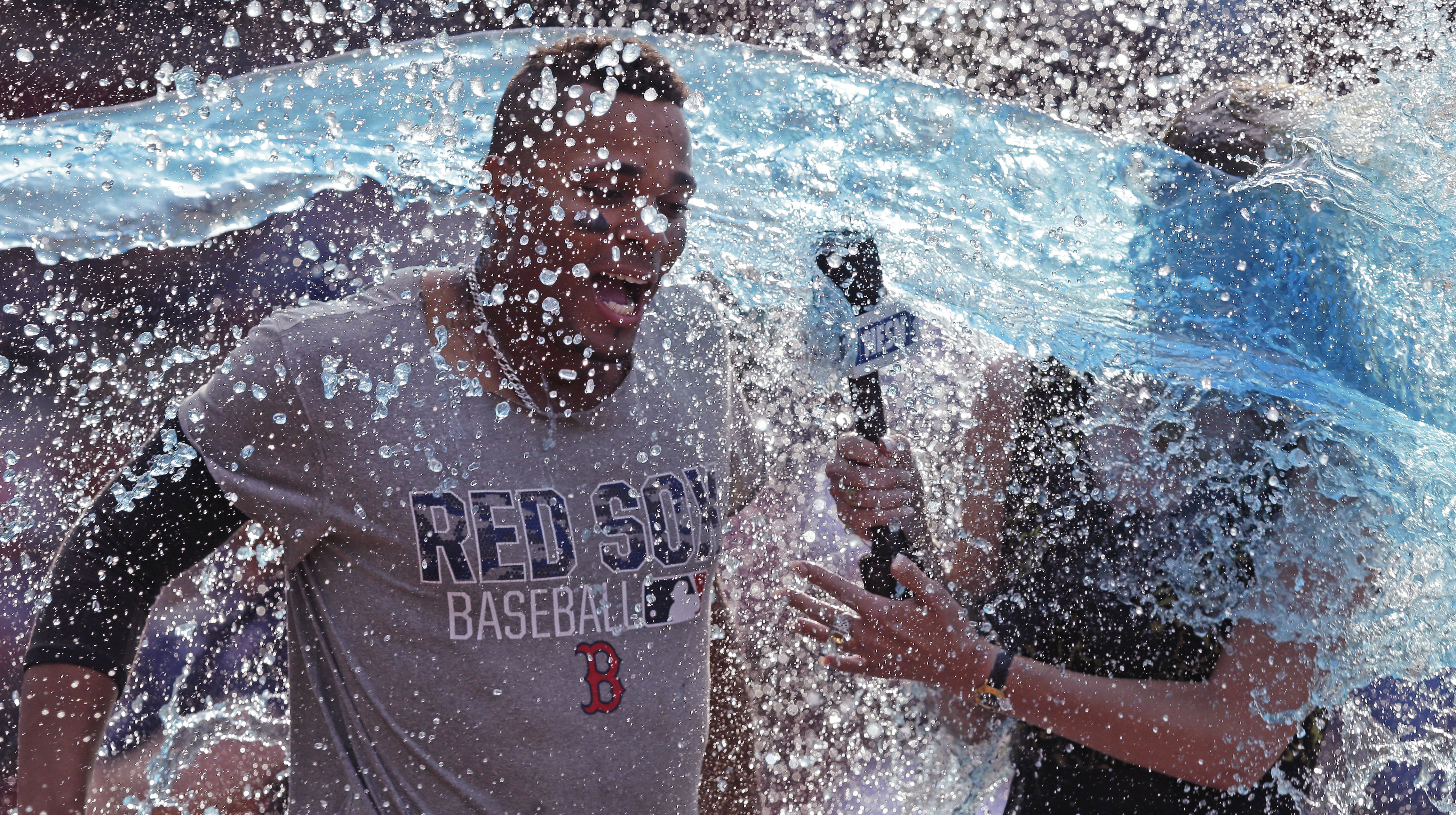 Boston Red Sox's Xander Bogaerts, left, and TV reporter Guerin Austin are doused following Bogaert's' walkoff RBI-single during the 10th inning of a baseball game against the Chicago White Sox at Fenway Park, Thursday, June 23, 2016, in Boston. (AP Photo/