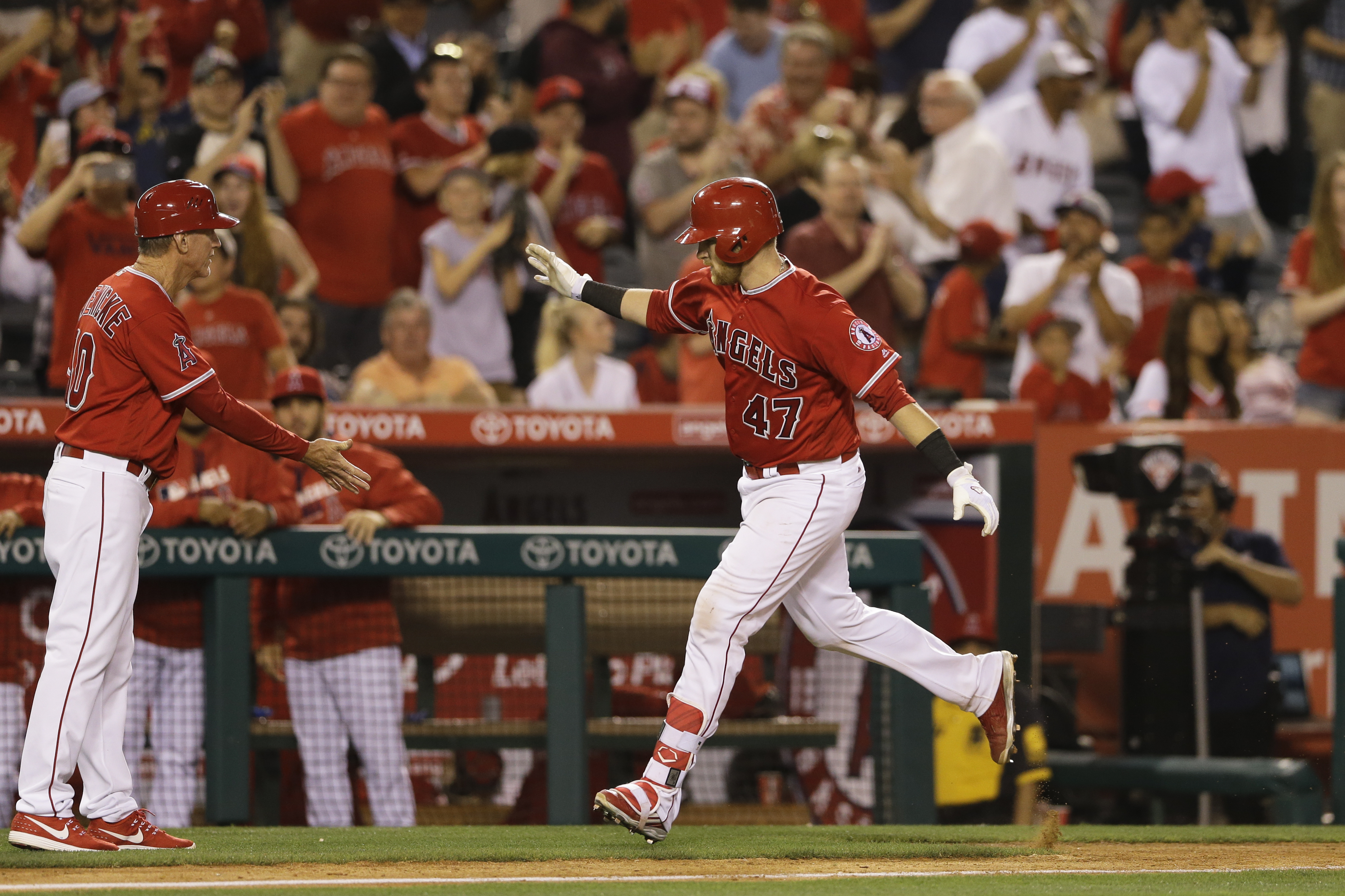 Los Angeles Angels' Jett Bandy (47) is greeted by third base coach Ron Roenicke after hitting a two-run home run during the ninth inning of a baseball game Thursday, June 23, 2016, in Anaheim, Calif. (AP Photo/Gregory Bull)