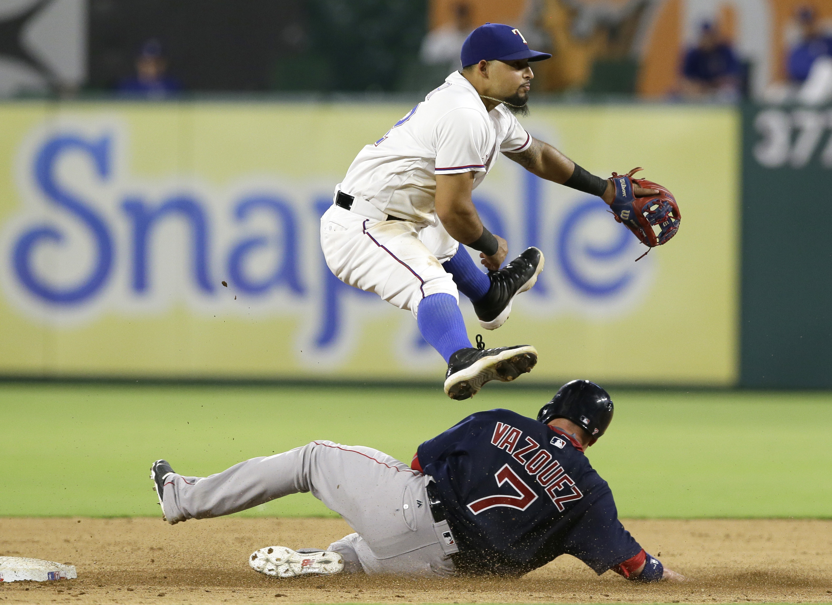 Texas Rangers second baseman Rougned Odor jumps as Boston Red Sox Christian Vazquez (7) slides into second base after being forced out on the first half of a double play during the fifth inning of a baseball game in Arlington, Texas, Friday, June 24, 2016