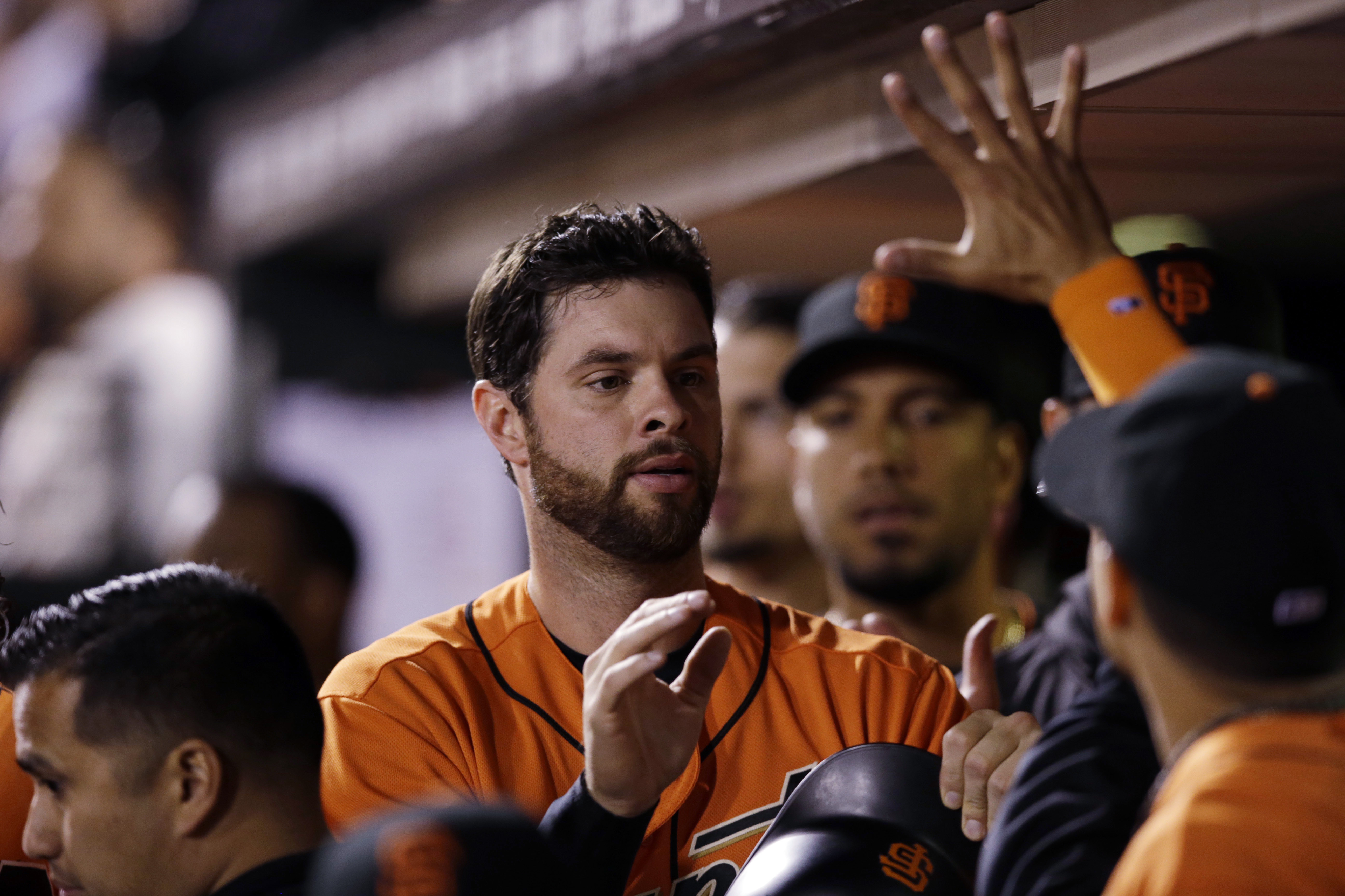 San Francisco Giants' Brandon Belt, center, is greeted in the dugout after scoring on a single by Angel Pagan during the seventh inning of a baseball game against the Philadelphia Phillies on Friday, June 24, 2016, in San Francisco. (AP Photo/Marcio Jose