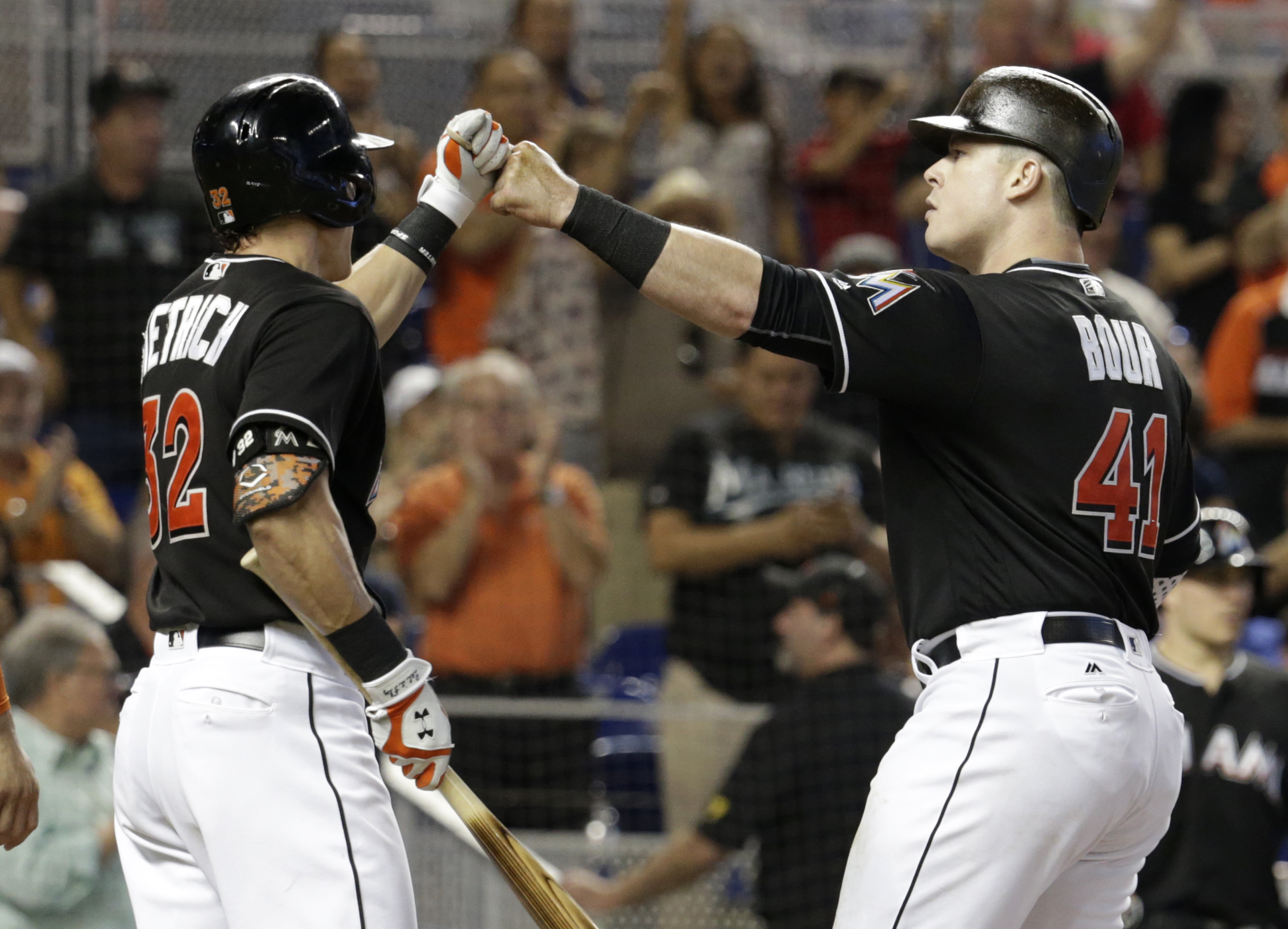 Miami Marlins' Justin Bour (41) is met by Derek Dietrich (32) at the plate after scoring on a two-run home run during the fourth inning of a baseball game against the Chicago Cubs, Saturday, June 25, 2016, in Miami. (AP Photo/Lynne Sladky)