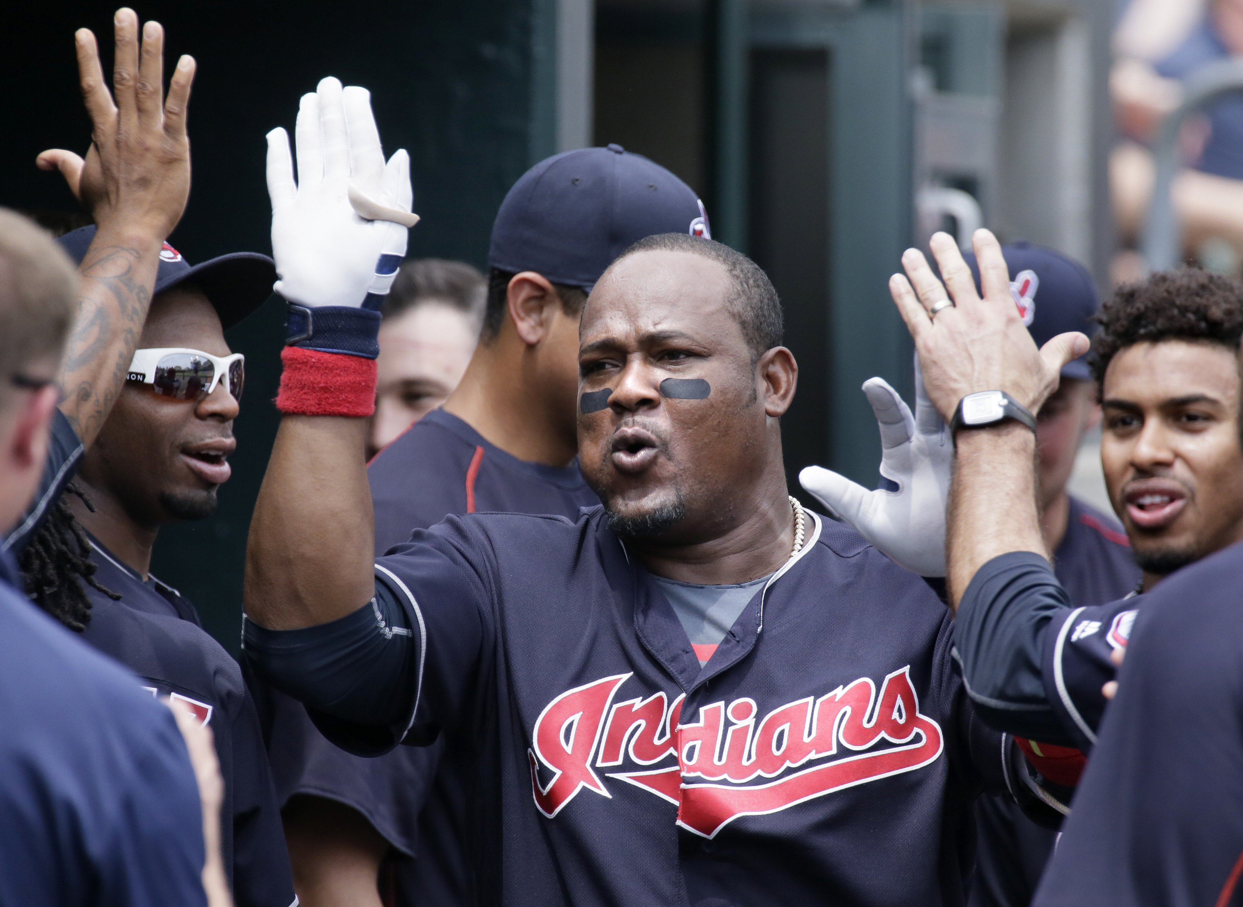 Cleveland Indians' Juan Uribe celebrates in the dugout after hitting a solo home run against the Detroit Tigers during the fifth inning of a baseball game Sunday, June 26, 2016, in Detroit. (AP Photo/Duane Burleson)