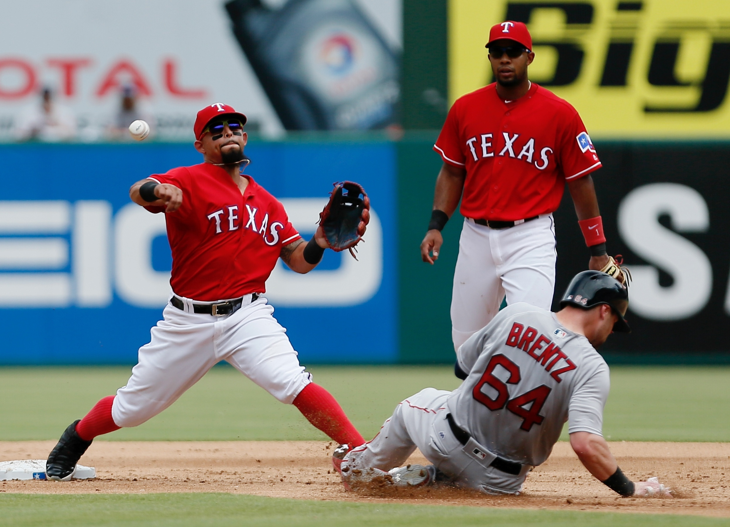Texas Rangers shortstop Elvis Andrus, top right, looks on as second baseman Rougned Odor, left, throws to first for a double play forcing out Boston Red Sox's Bryce Brentz (64) and Travis Shaw, during the second inning of a baseball game Sunday, June 26,