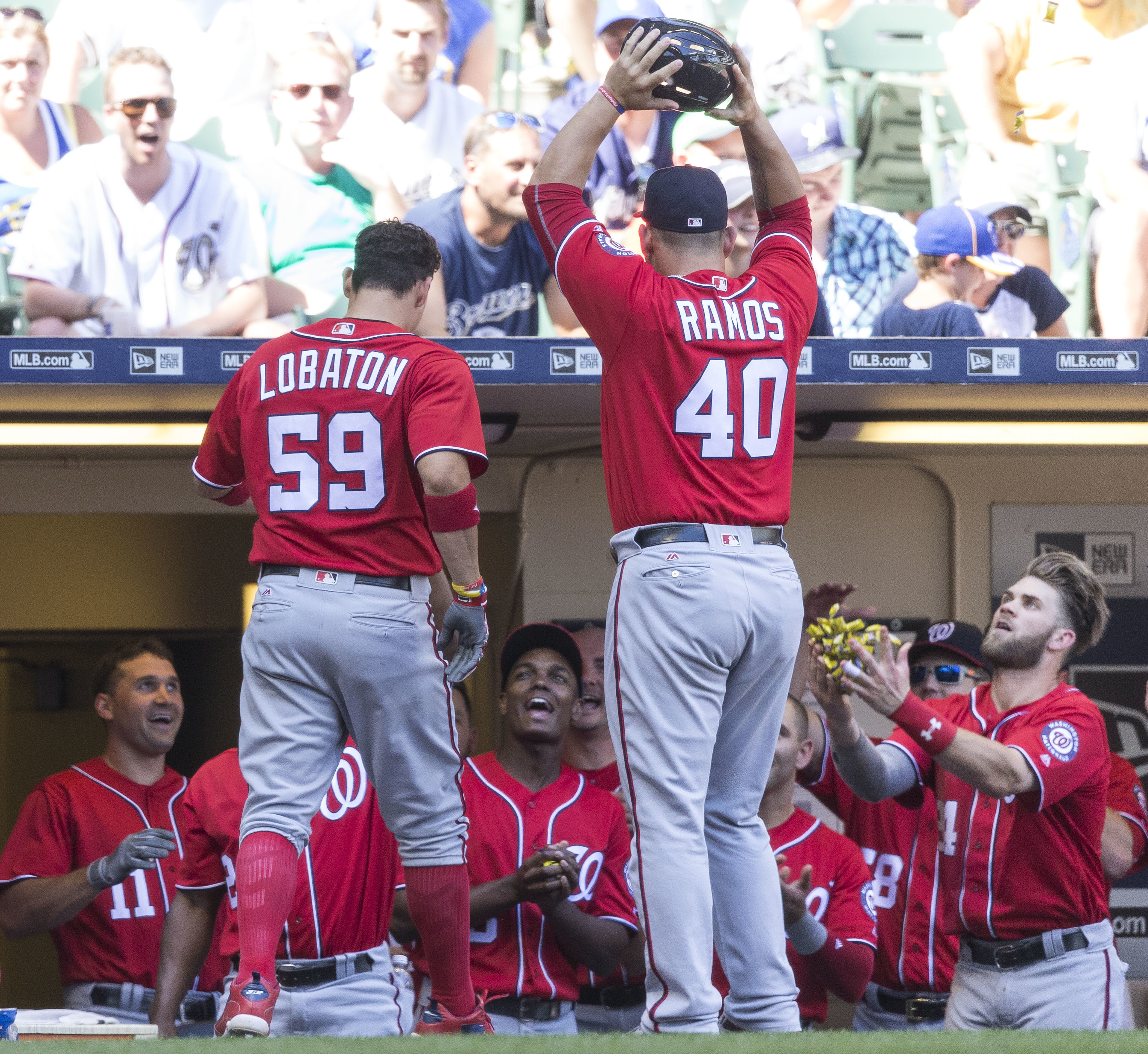 Washington Nationals' Jose Lobaton (59) is greeted by teammates after hitting a solo home run off Milwaukee Brewers' Jacob Barnes during the seventh inning of a baseball game Sunday, June 26, 2016, in Milwaukee. (AP Photo/Tom Lynn)