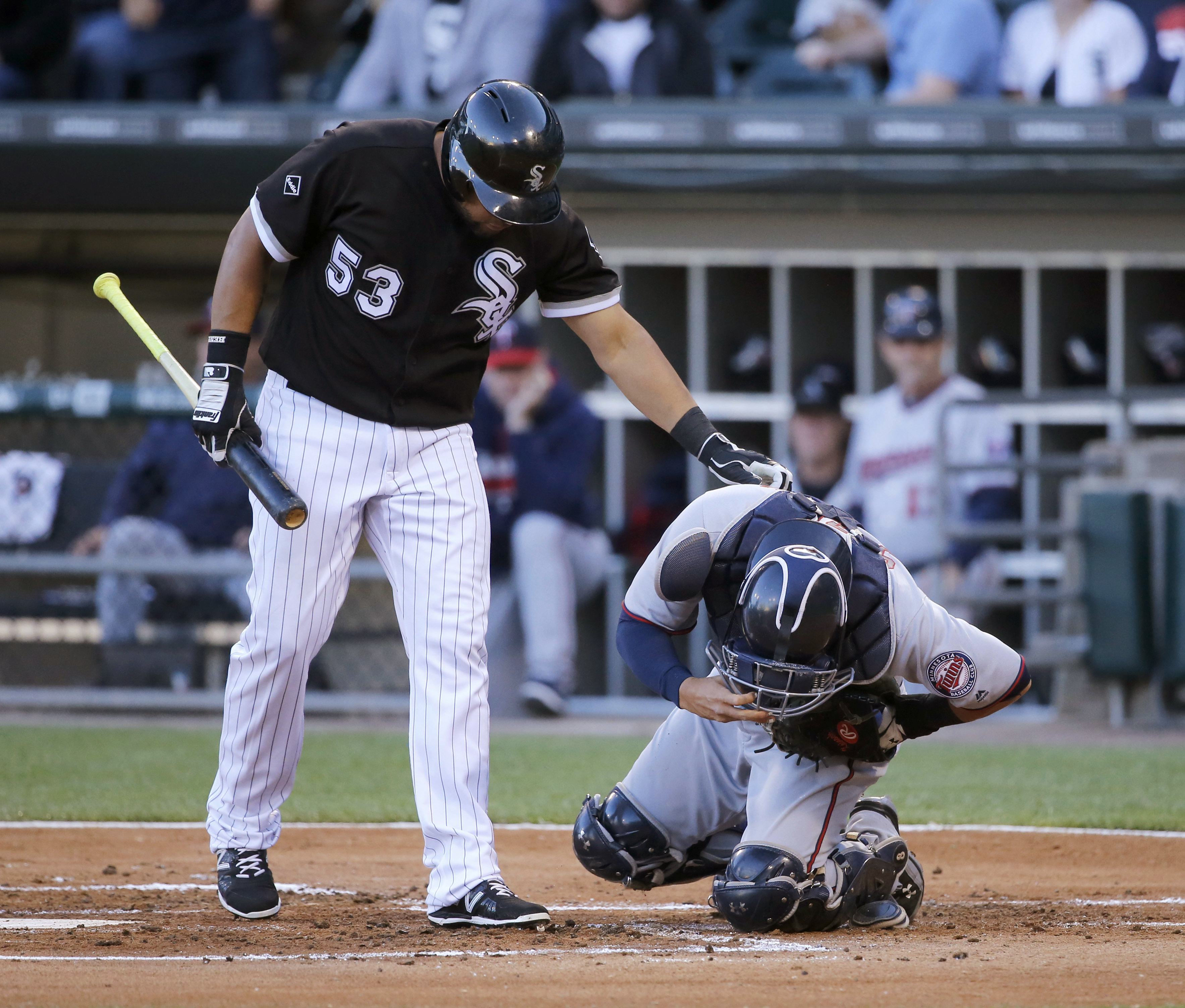 Chicago White Sox's Melky Cabrera checks on Minnesota Twins catcher Kurt Suzuki after Suzuki was hit on the arm byCabrera's foul ball during the first inning of a baseball game Tuesday, June 28, 2016, in Chicago. (AP Photo/Charles Rex Arbogast)