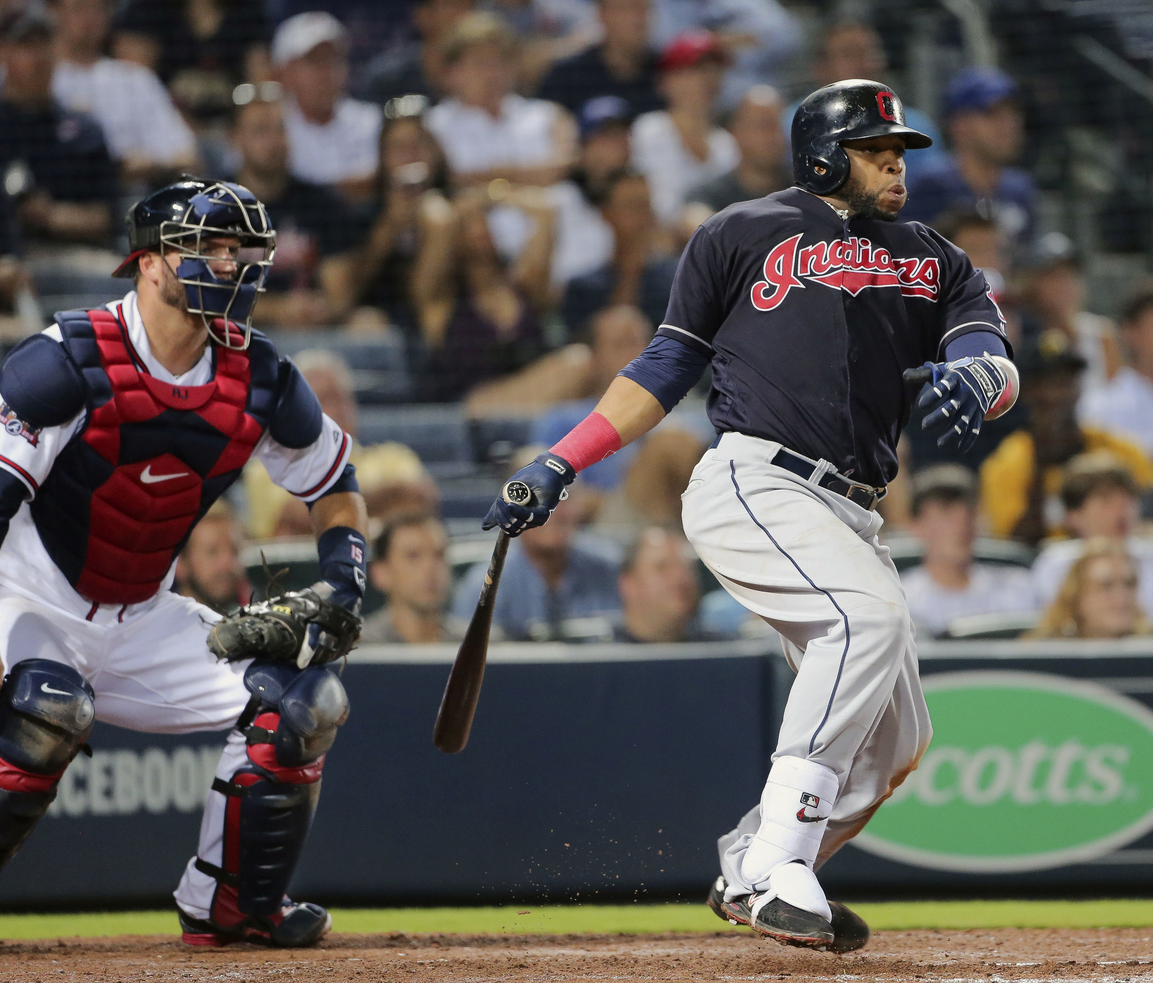 Cleveland Indians' Carlos Santana, right, drives in a run with a base as Atlanta Braves catcher A.J. Pierzynski looks on in the ninth inning of a baseball game Tuesday, June 28, 2016, in Atlanta. (AP Photo/John Bazemore)