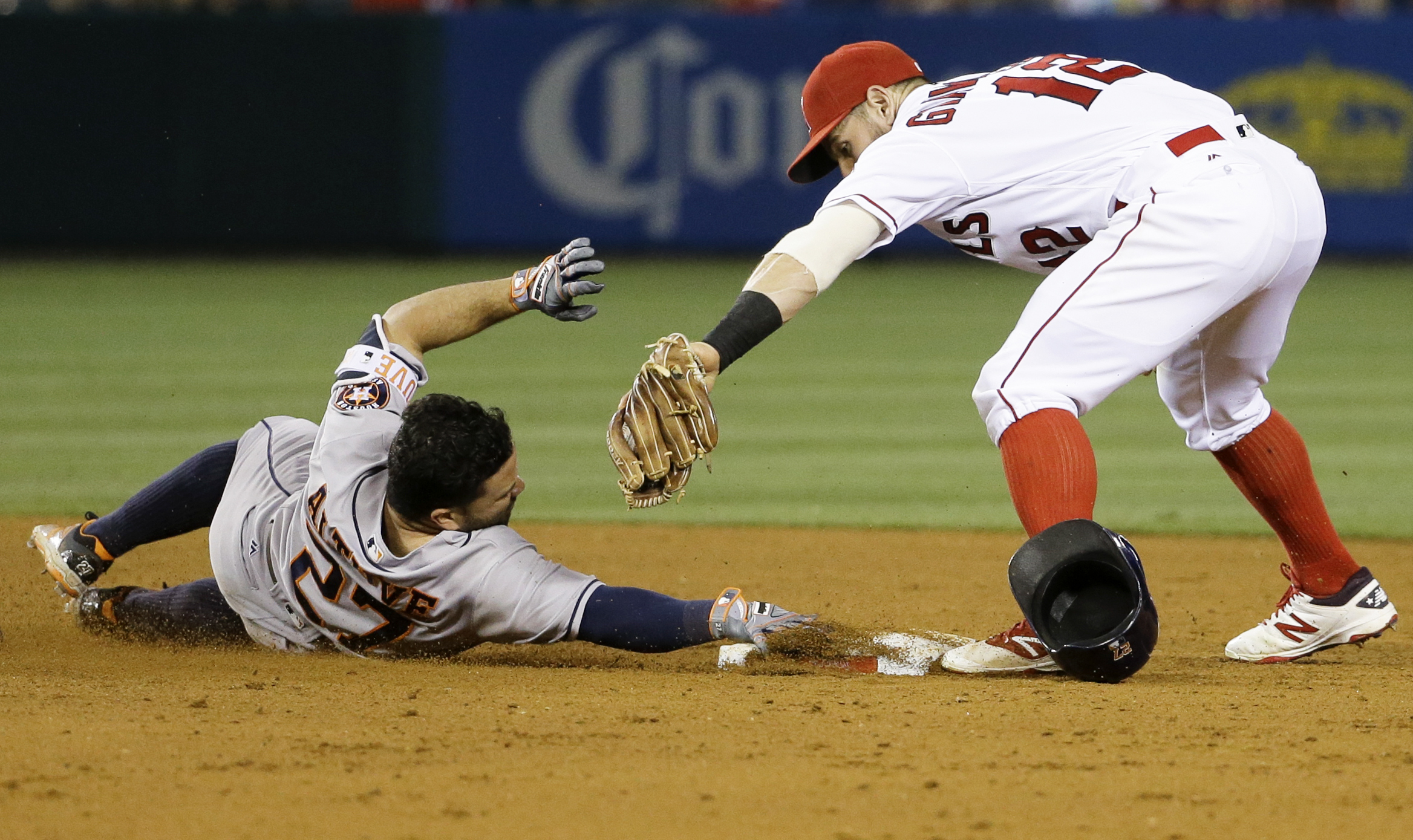 Houston Astros' Jose Altuve, left, tries to avoid the tag as he slides off second base before being tagged out by Los Angeles Angels second baseman Johnny Giavotella (12) during the fifth inning of a baseball game Tuesday, June 28, 2016, in Anaheim, Calif