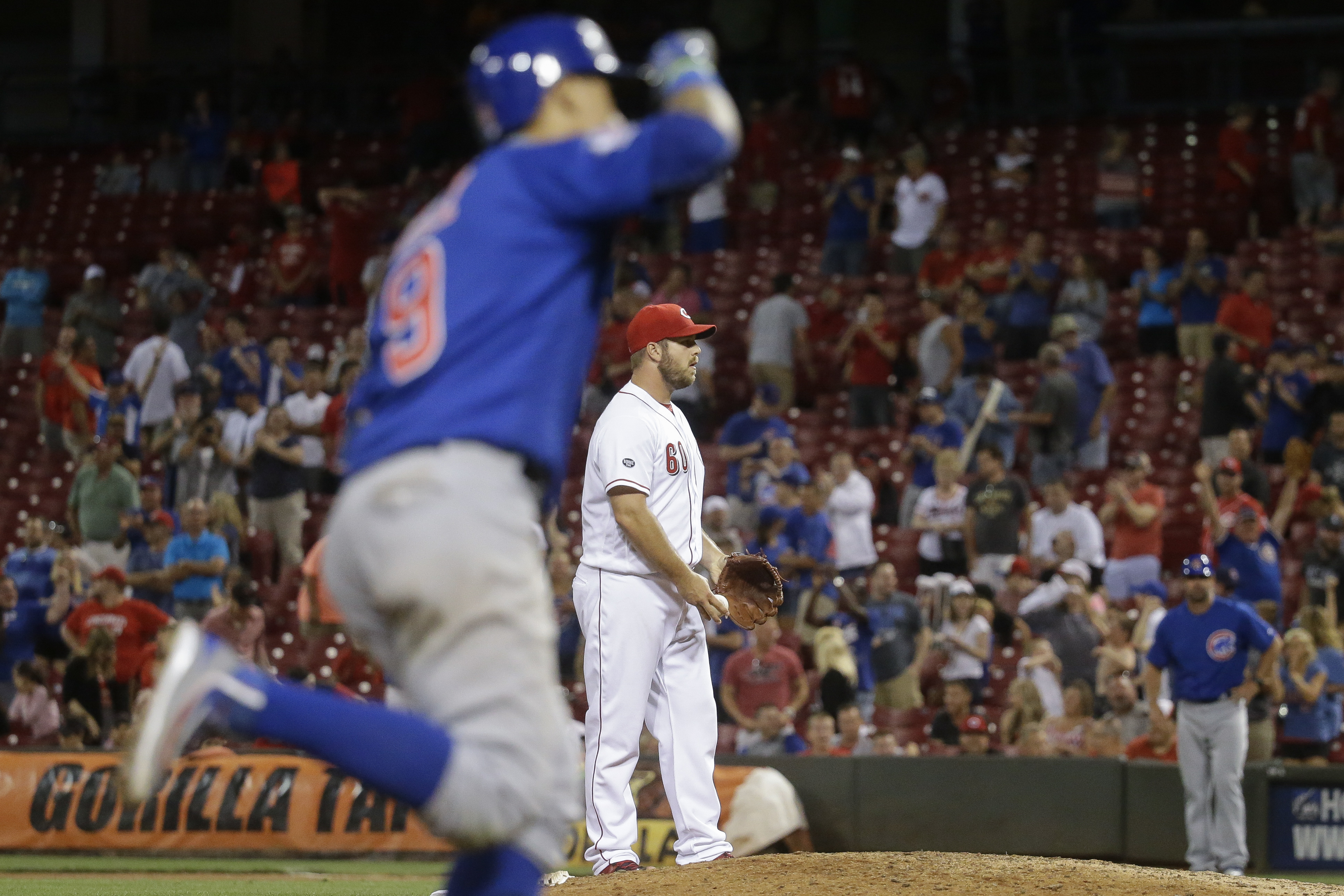 Cincinnati Reds relief pitcher J.J. Hoover stands on the mound as Chicago Cubs' Javier Baez (9) runs the bases on a grand slam in the 15th inning of a baseball game, Tuesday, June 28, 2016, in Cincinnati. The Cubs won 7-2. (AP Photo/John Minchillo)