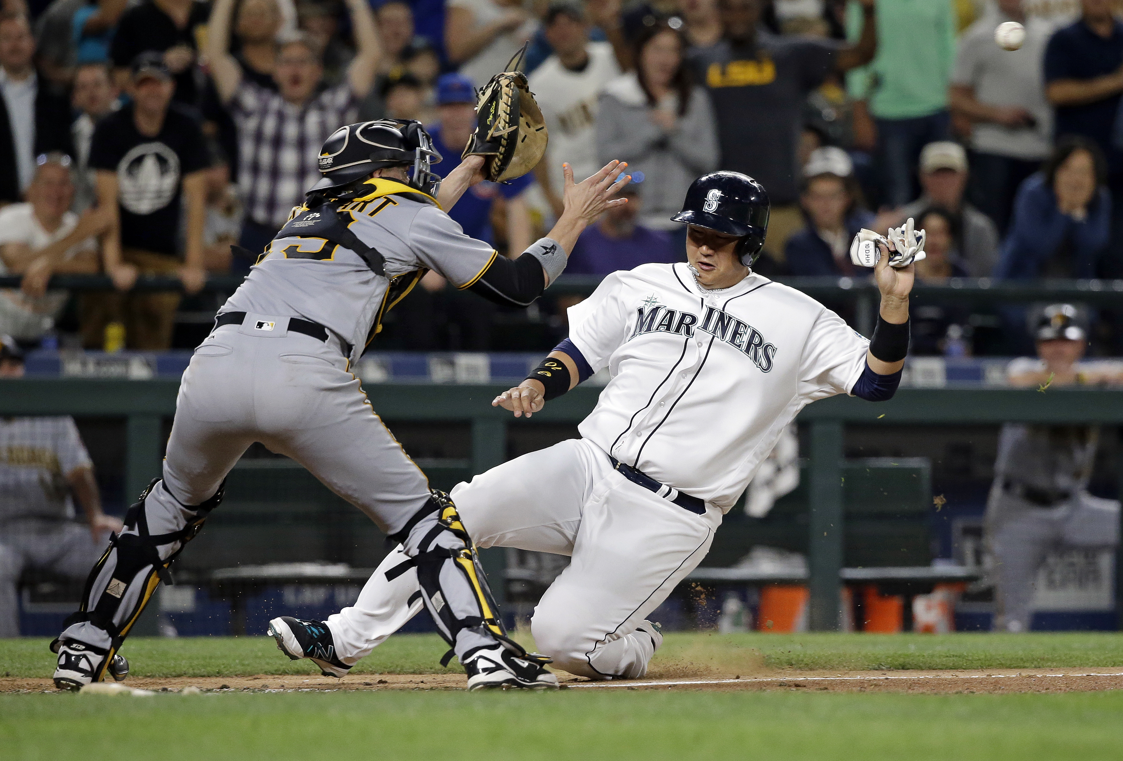 Seattle Mariners' Dae-Ho Lee, right, slides toward Pittsburgh Pirates catcher Chris Stewart before being tagged out at home during the seventh inning of a baseball game Tuesday, June 28, 2016, in Seattle. (AP Photo/Elaine Thompson)