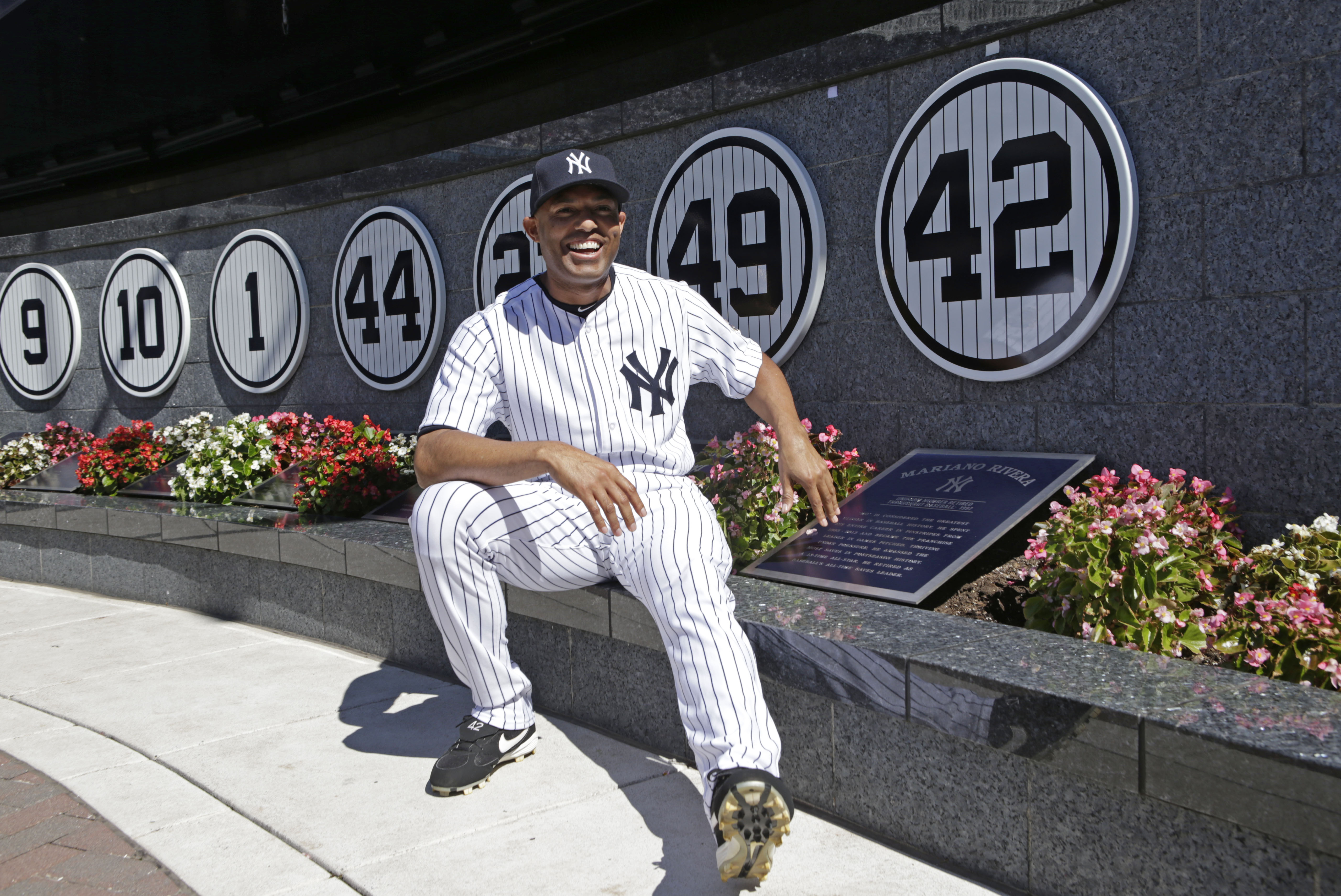 New York Yankees relief pitcher Mariano Rivera (42) sits beside his retired number in Monument Park during a pregame ceremony at Yankee Stadium before the Yankees baseball game against the San Francisco Giants, Sunday, Sept. 22, 2013, in New York. (AP Pho
