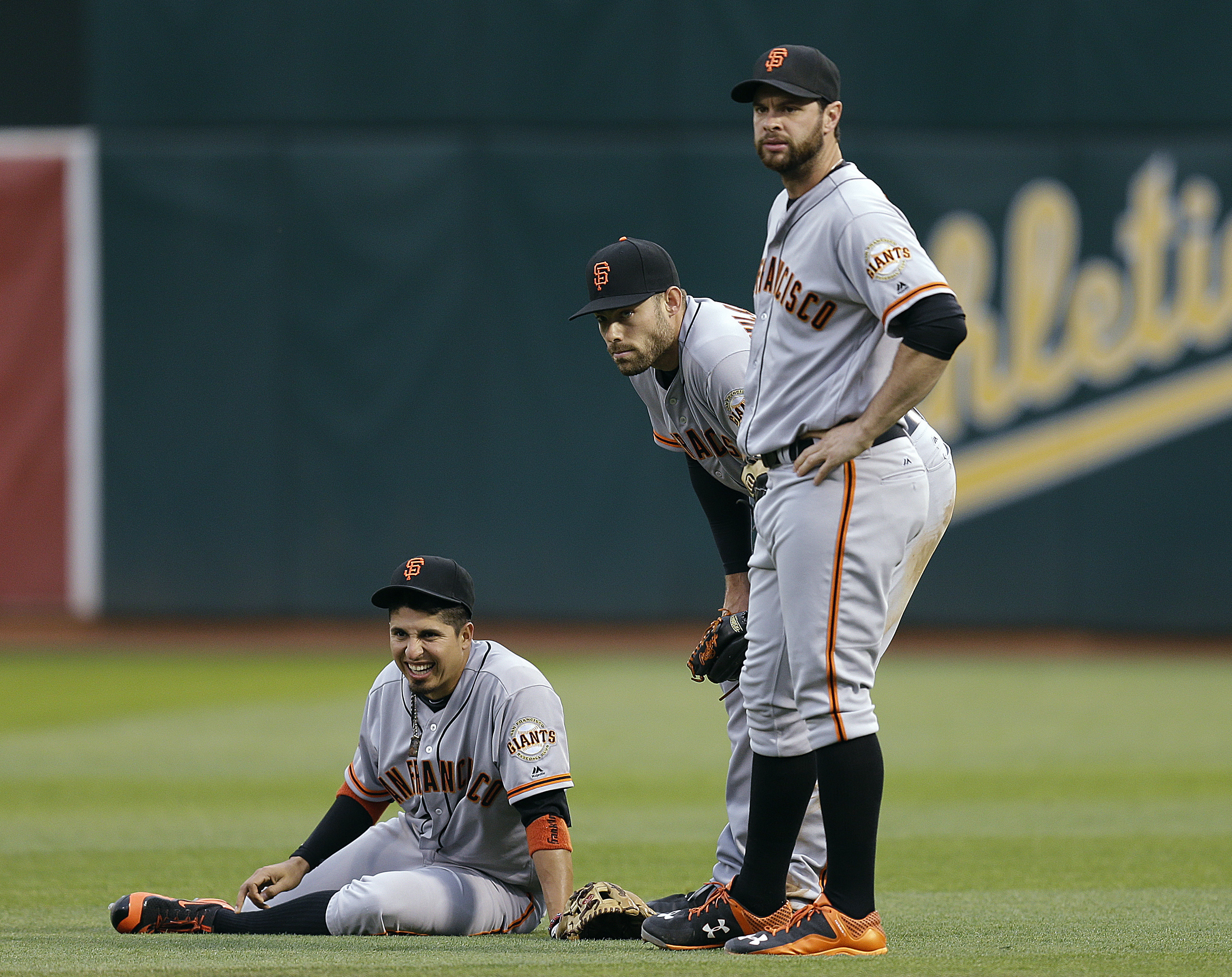 San Francisco Giants second baseman Raul Pena, left, waits for a trainer after colliding with outfielder Mac Williamson, center, during the third inning of a baseball game against the Oakland Athletics on Wednesday, June 29, 2016, in Oakland, Calif. At ri