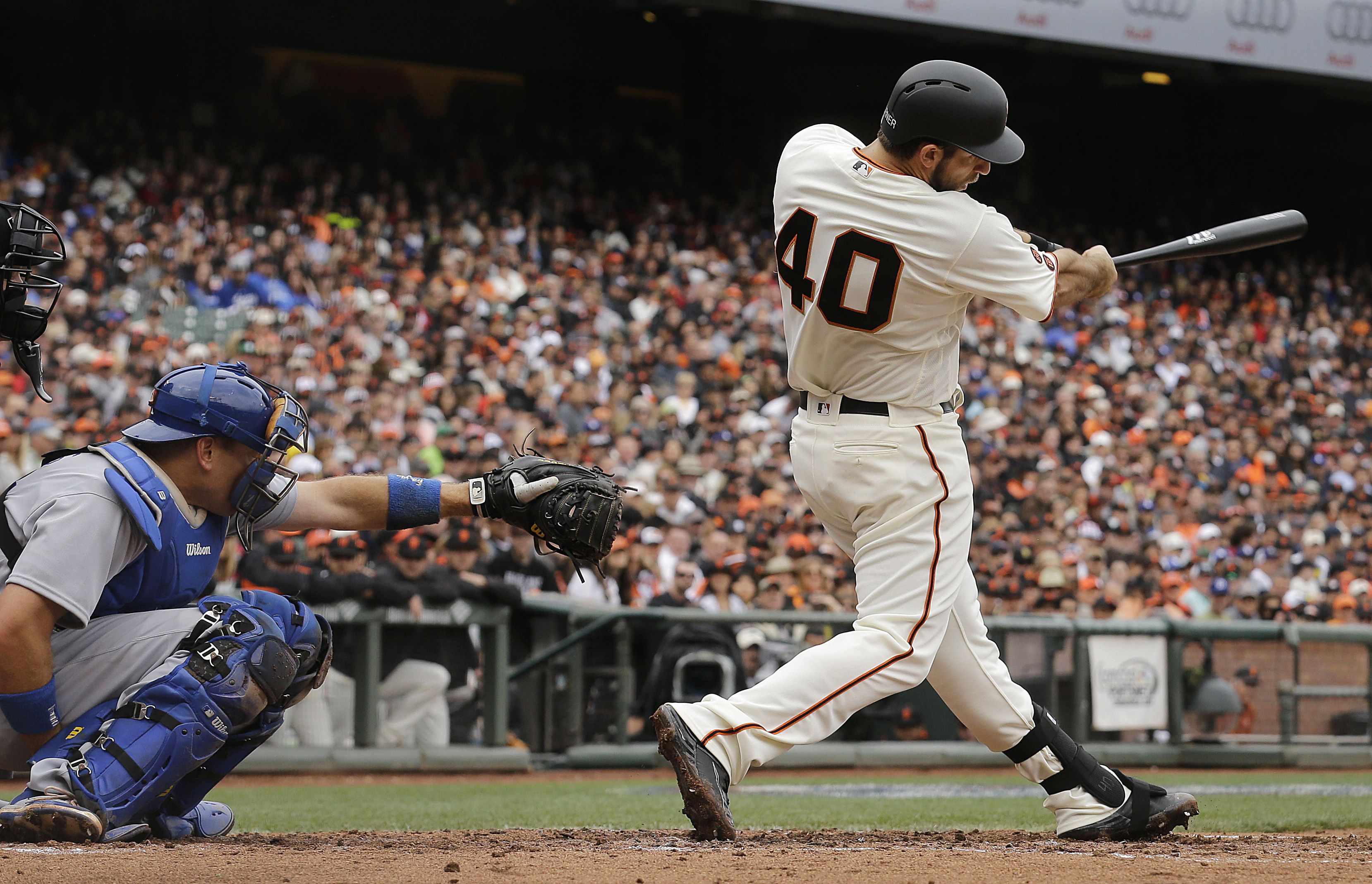 FILE - In this April 9, 2016, file photo, San Francisco Giants' Madison Bumgarner (40) hits a solo home run in front of Los Angeles Dodgers catcher A.J. Ellis during the second inning of a baseball game in San Francisco. San Francisco manager Bruce Bochy