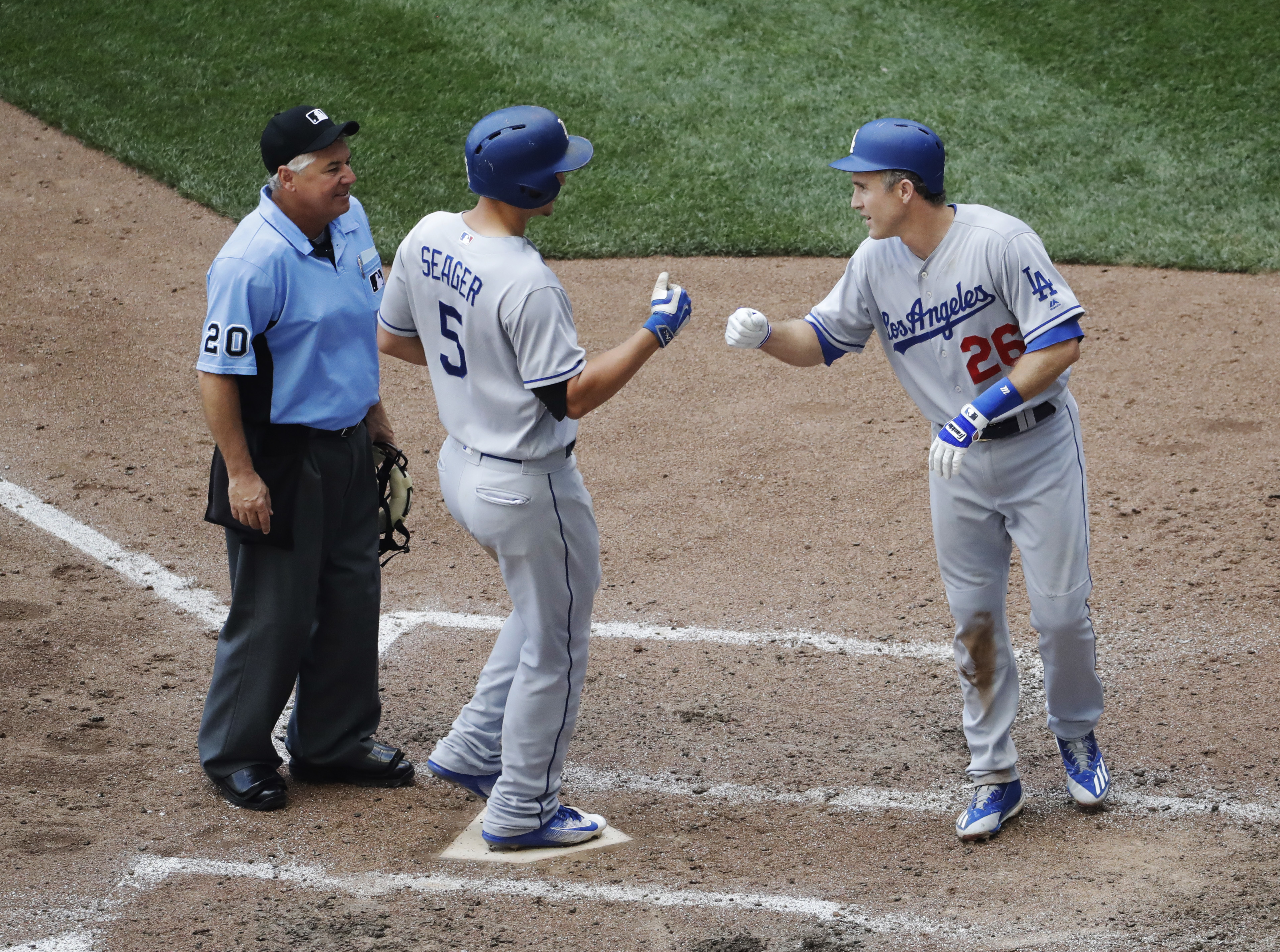 Los Angeles Dodgers' Corey Seager is congratulated by Chase Utley after hitting a two-run home run during the fifth inning of a baseball game against the Milwaukee Brewers Thursday, June 30, 2016, in Milwaukee. (AP Photo/Morry Gash)