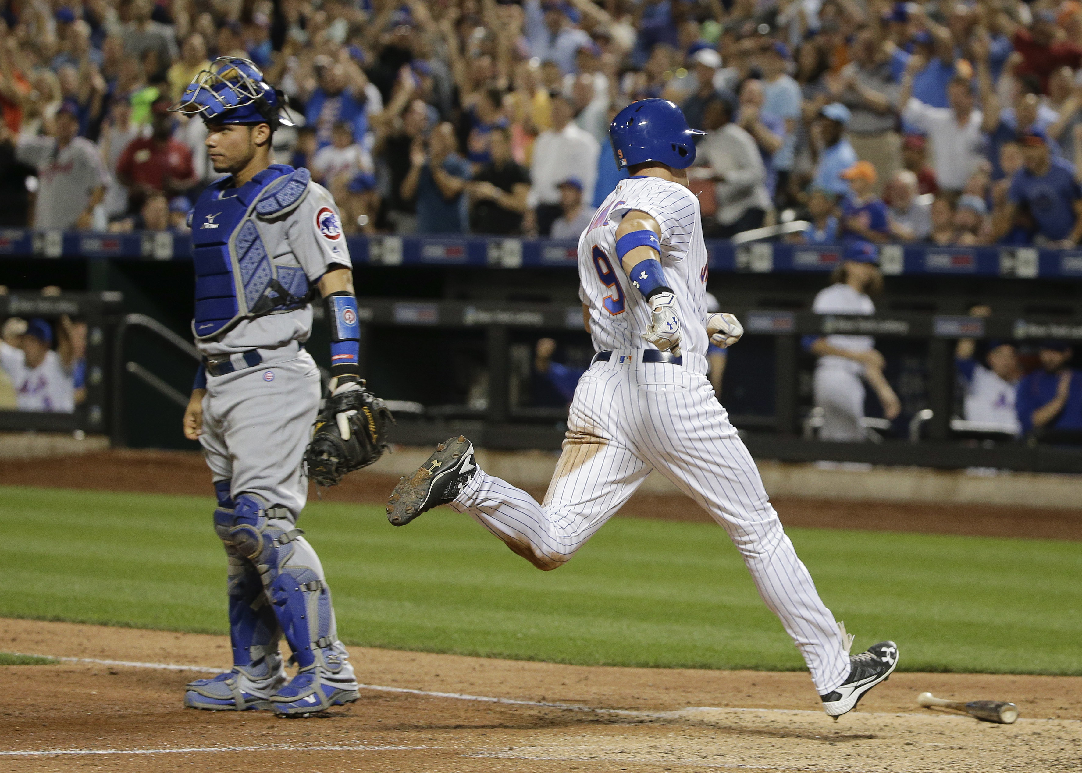New York Mets' Brandon Nimmo (9) scores on an error by Chicago Cubs second baseman Javier Baez during the seventh inning of a baseball game, Thursday, June 30, 2016, in New York. Cubs catcher Willson Contreras is at left. (AP Photo/Julie Jacobson)