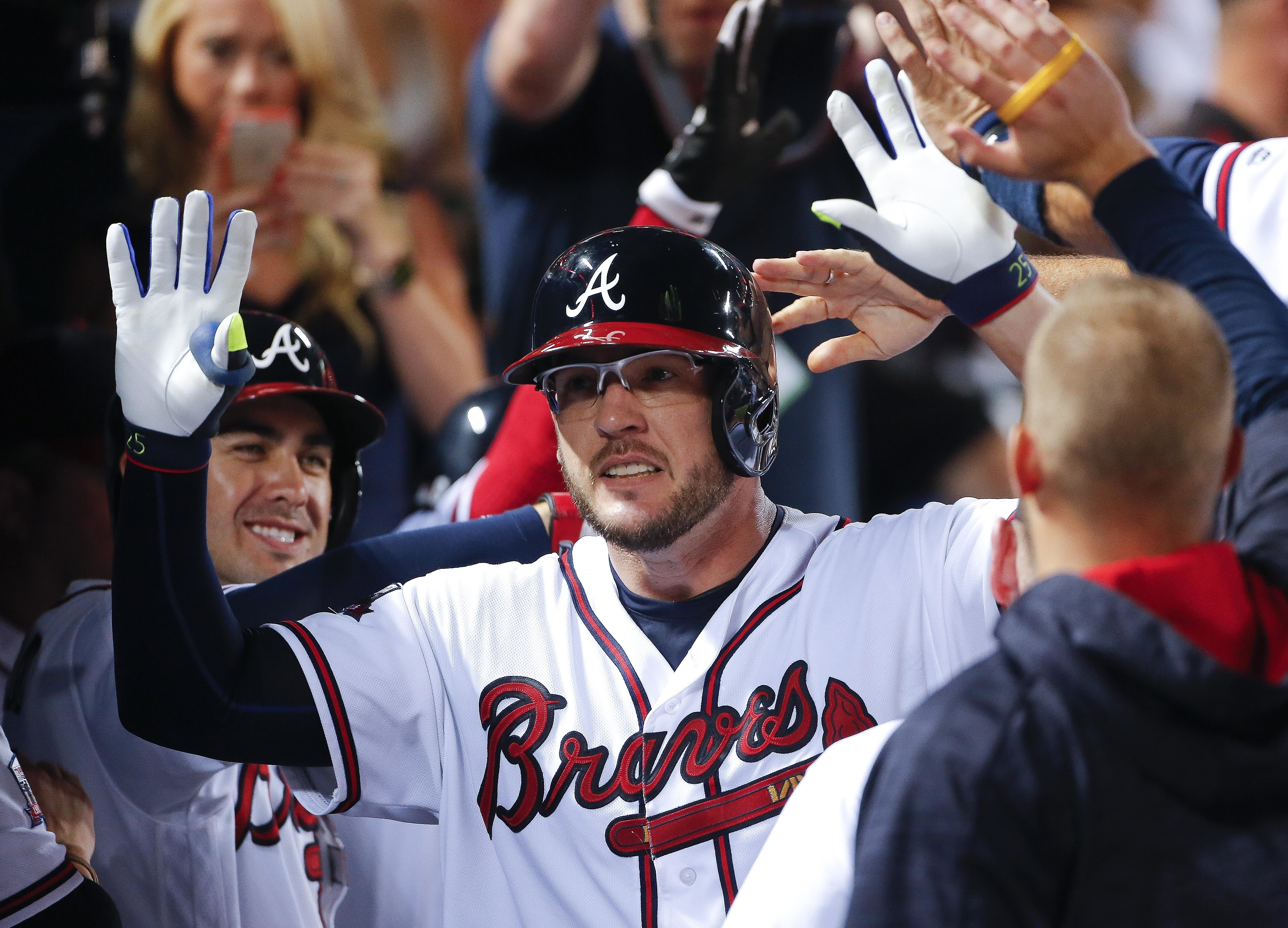 Atlanta Braves' Tyler Flowers celebrates in the dugout after hitting a game-tying home run in the ninth inning of a baseball game against the Miami Marlins, Friday, July 1, 2016, in Atlanta. (AP Photo/John Bazemore)