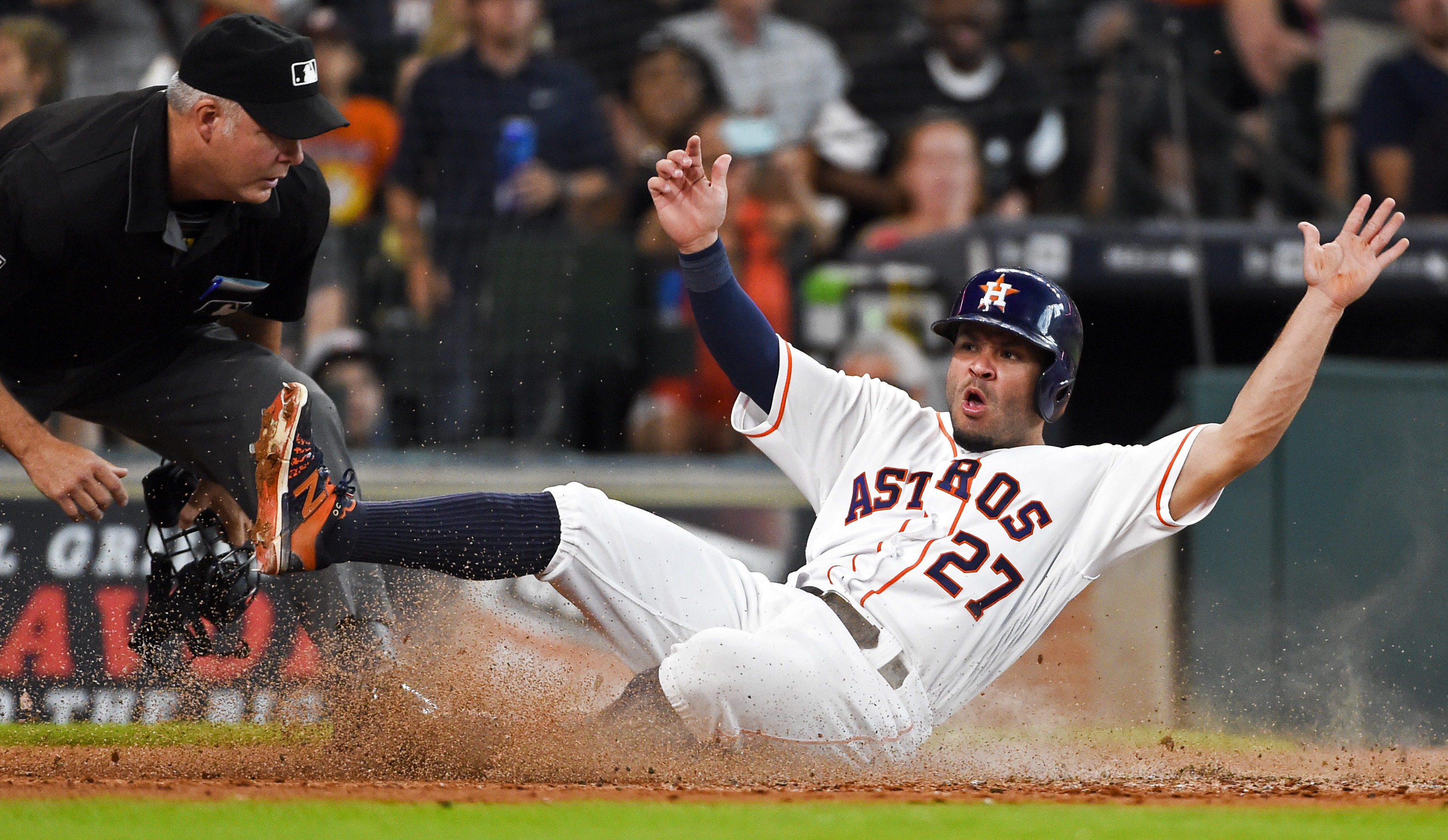 Houston Astros' Jose Altuve (27) slides safely at home to score on Carlos Correa's RBI-single as home plate umpire Tim Timmons looks on in the third inning of a baseball game against the Chicago White Sox, Saturday, July 2, 2016, in Houston. (AP Photo/Eri
