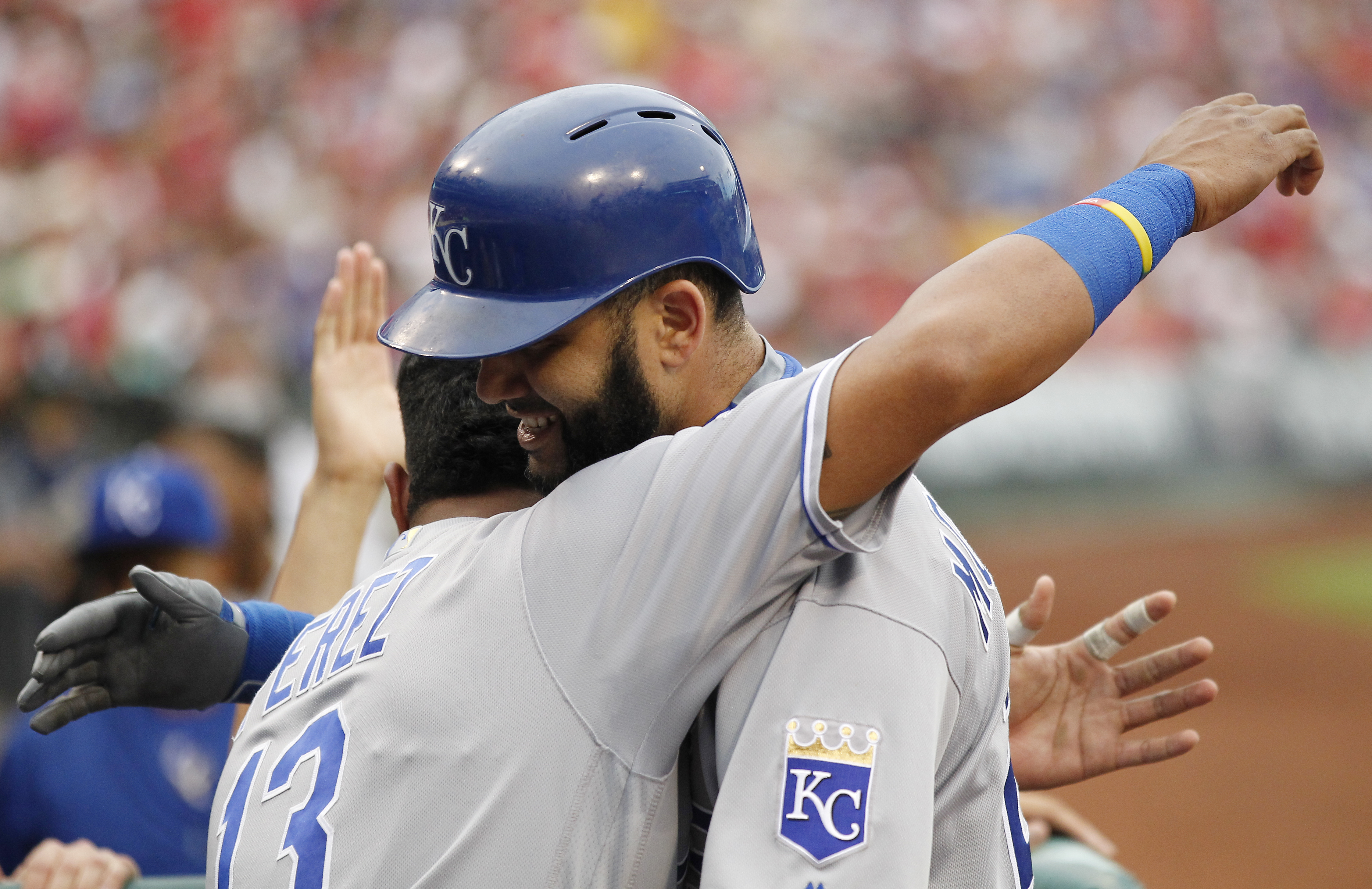 Kansas City Royals' Salvador Perez, left, hugs Kendrys Morales who returns to the dugout after his three-run home run  during the second inning of a baseball game against the Philadelphia Phillies, Saturday, July 2, 2016, in Philadelphia. (AP Photo/Tom Mi