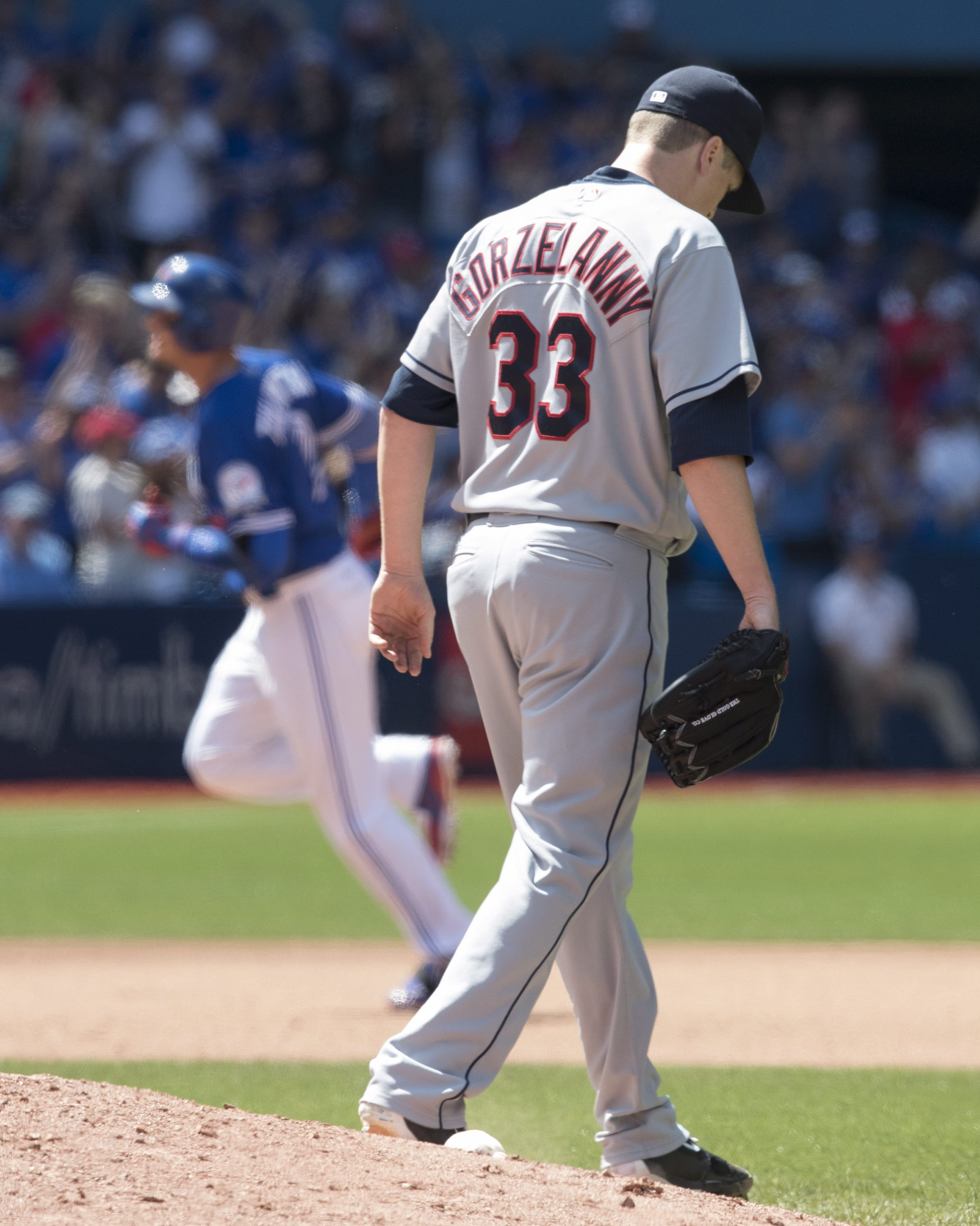 Cleveland Indians pitcher Tom Gorzelanny, right, walks off the mound after giving up a three-run home run to Toronto Blue Jays' Troy Tulowitzki circling the bases behind him during sixth inning baseball action in Toronto on Sunday, July 3, 2016.  (Fred Th
