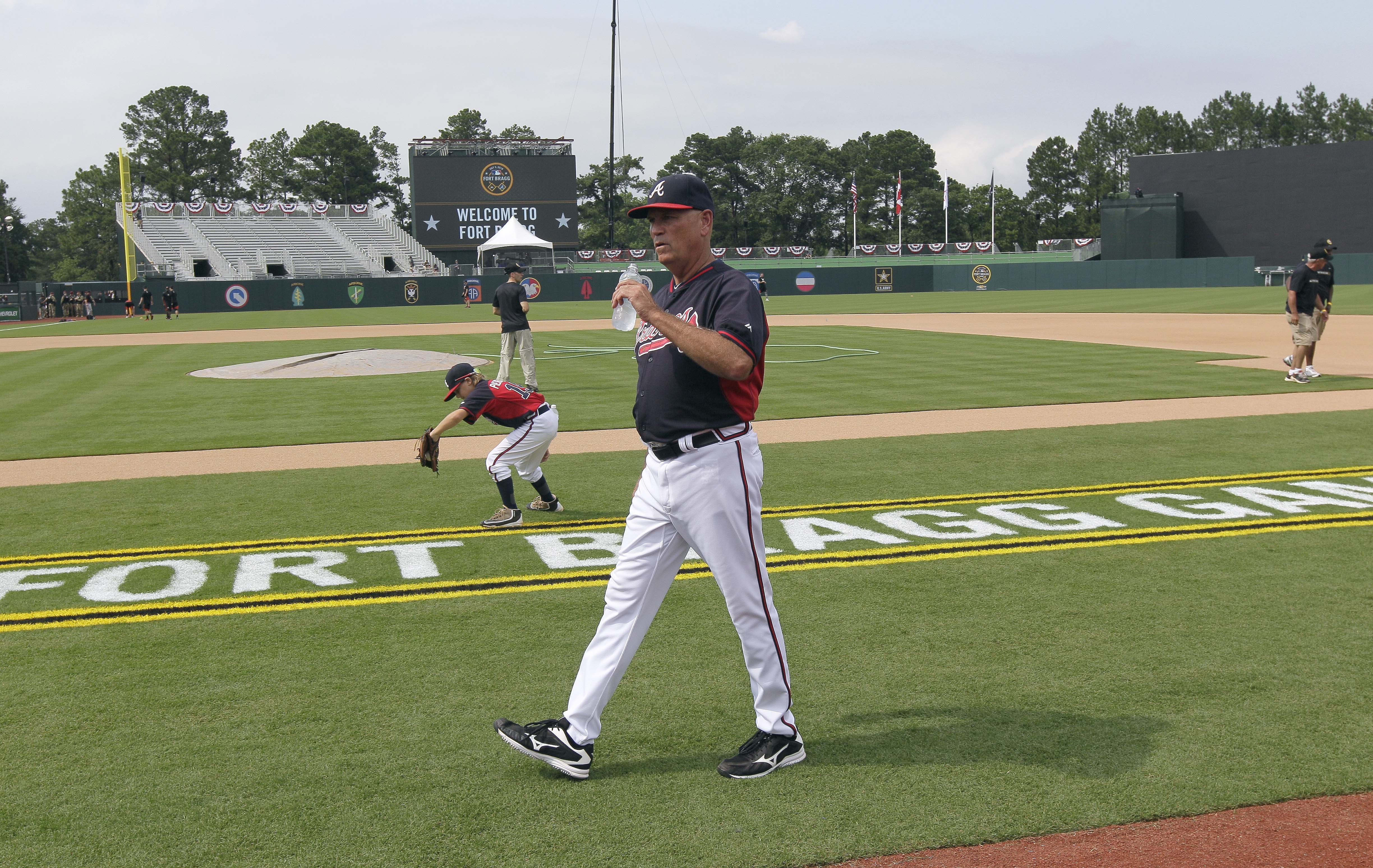 Atlanta Braves interim manager Brian Snitker (43) walks along the newly built baseball field prior to a game against the Miami Marlins in Fort Bragg, N.C., Sunday, July 3, 2016. (AP Photo/Gerry Broome)