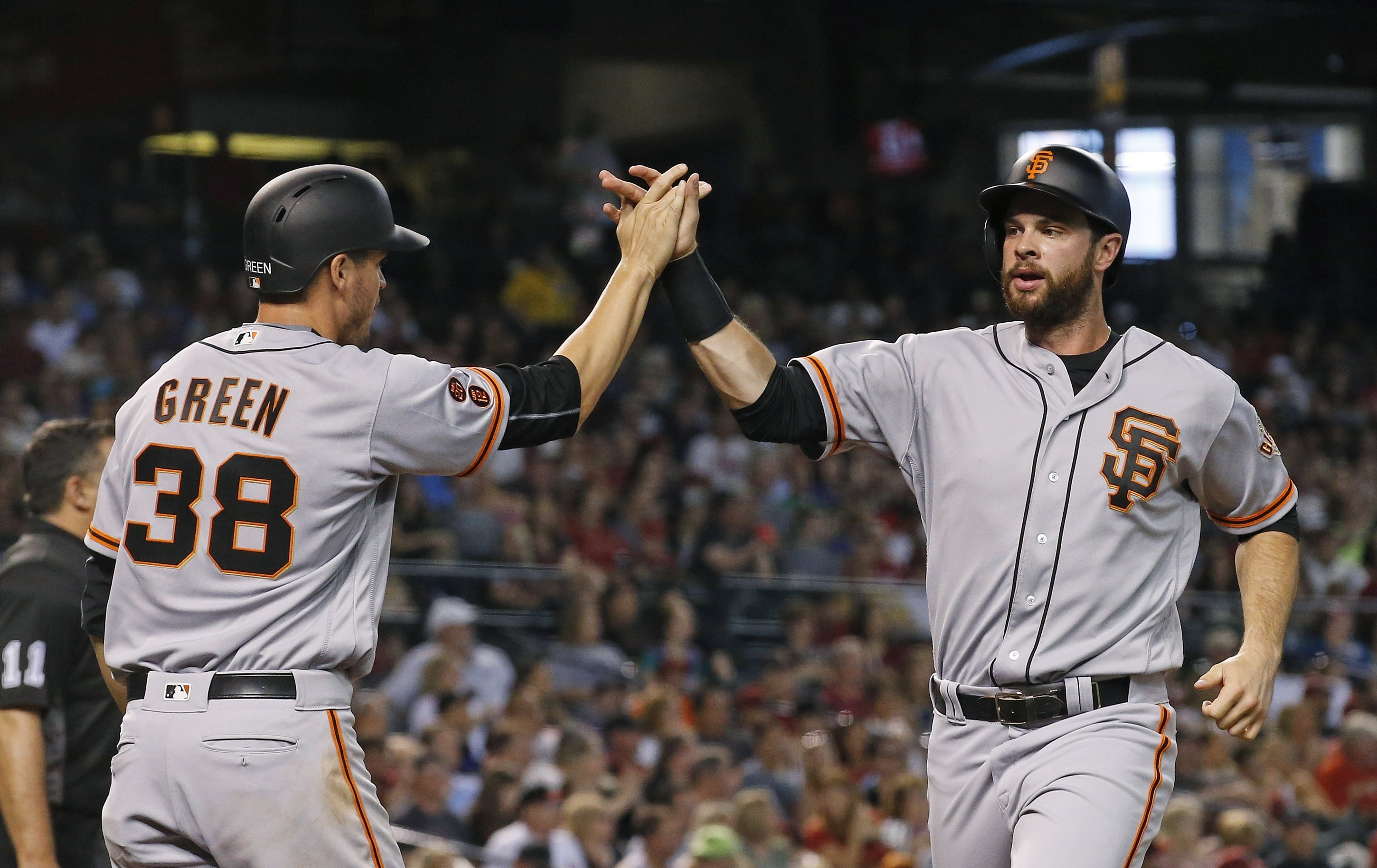 San Francisco Giants' Brandon Belt, right, and Grant Green (38) high-five after they scored runs against the Arizona Diamondbacks during the third inning of a baseball game Sunday, July 3, 2016, in Phoenix. (AP Photo/Ross D. Franklin)