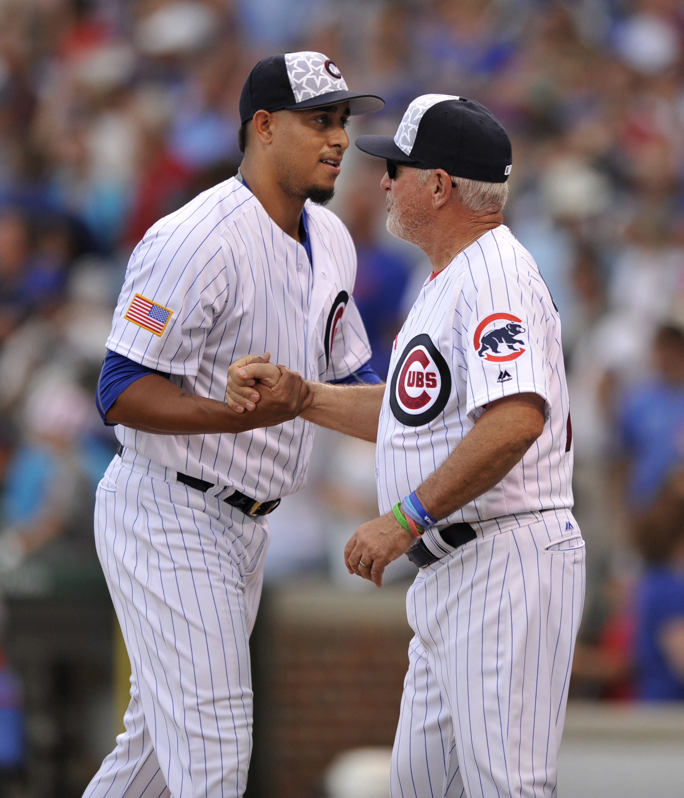 Chicago Cubs closing pitcher Hector Rondon left, celebrates with manager Joe Maddon right, after defeating the Cincinnati Reds in a baseball game Monday, July 4, 2016, in Chicago. (AP Photo/Paul Beaty)