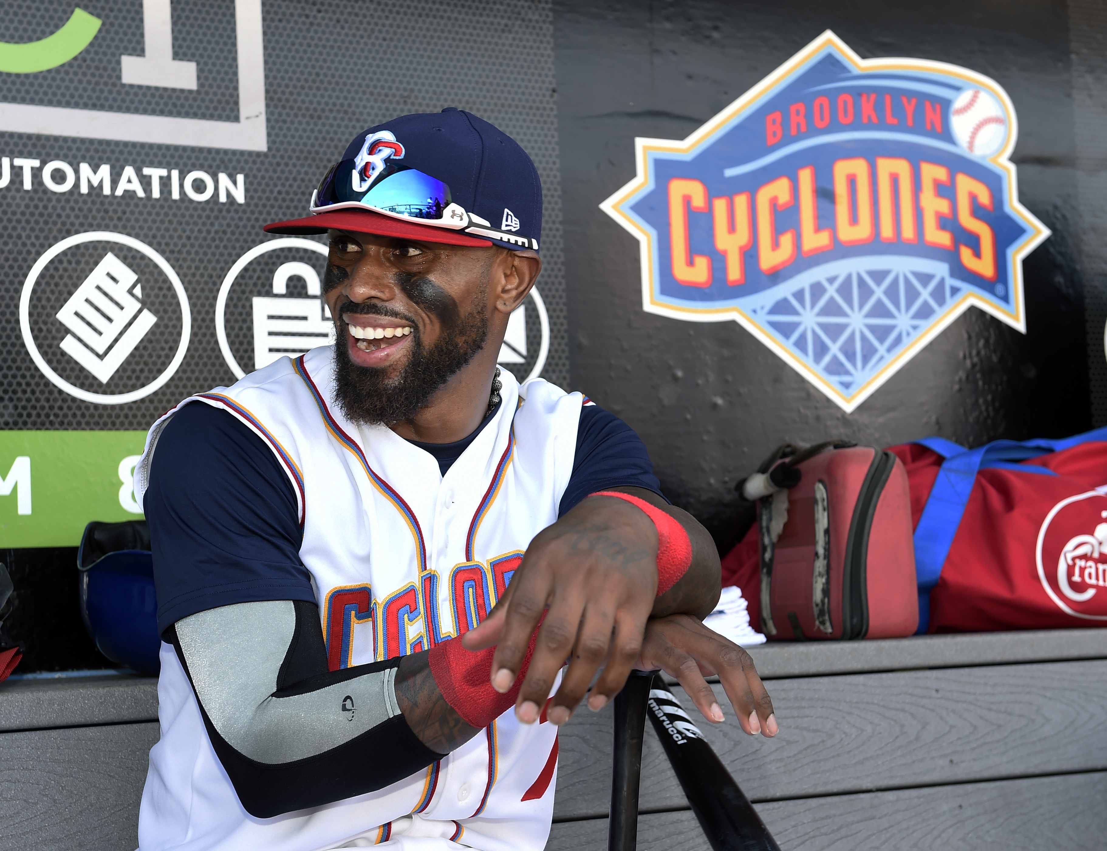 Brooklyn Cyclones Jose Reyes smiles as he rests his hands on his bat in the dugout before a minor league baseball game against the Hudson Valley Renegades, Sunday, June 26, 2016, in New York. Reyes, signed a minor league contract with the New York Mets on