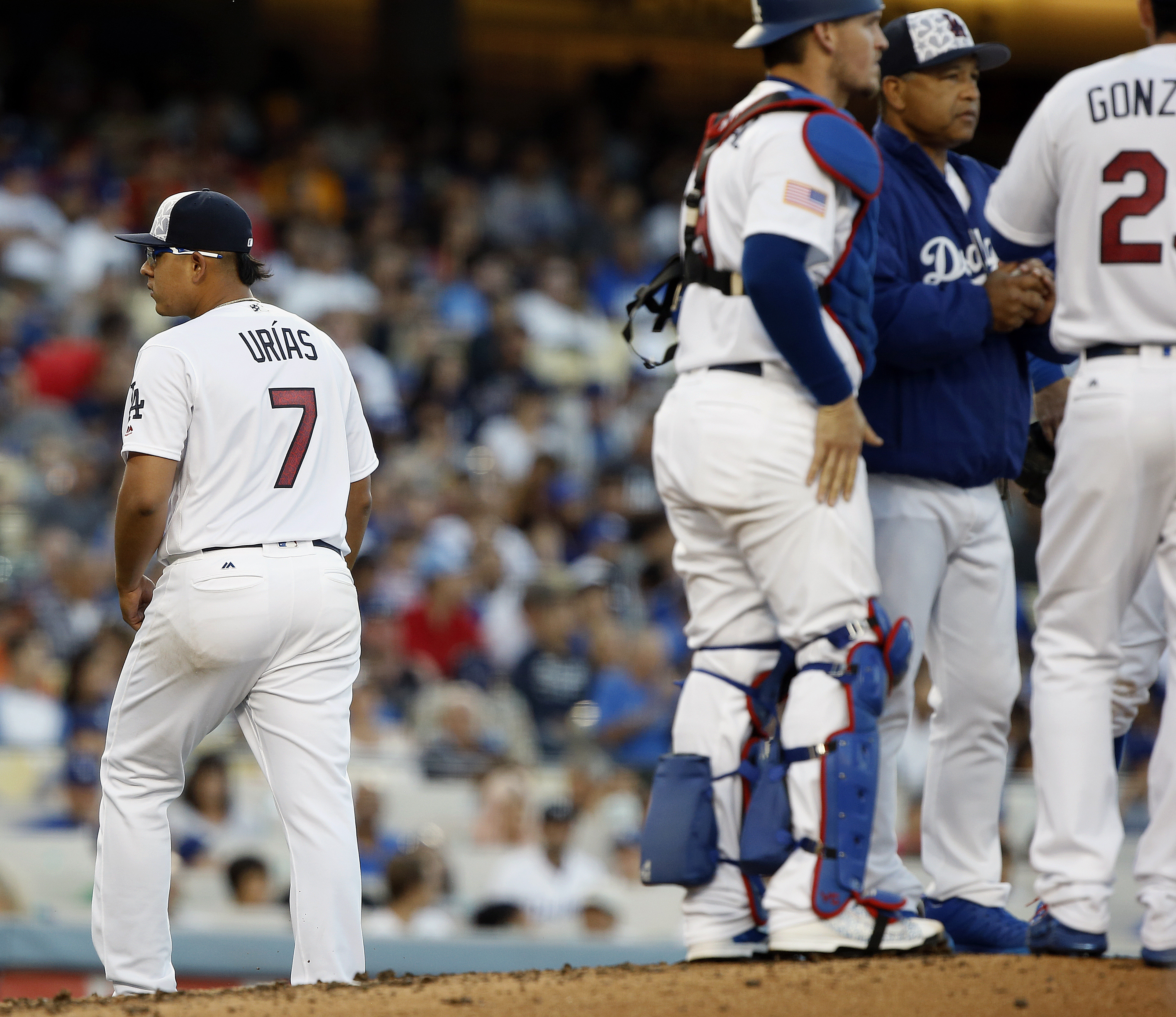 Los Angeles Dodgers starting pitcher Julio Urias (7) walks away from the mound after being pulled by manager Dave Roberts, second from right, with catcher Yasmani Grandal and first baseman Adrian Gonzalez, right, during the fourth inning of a baseball gam