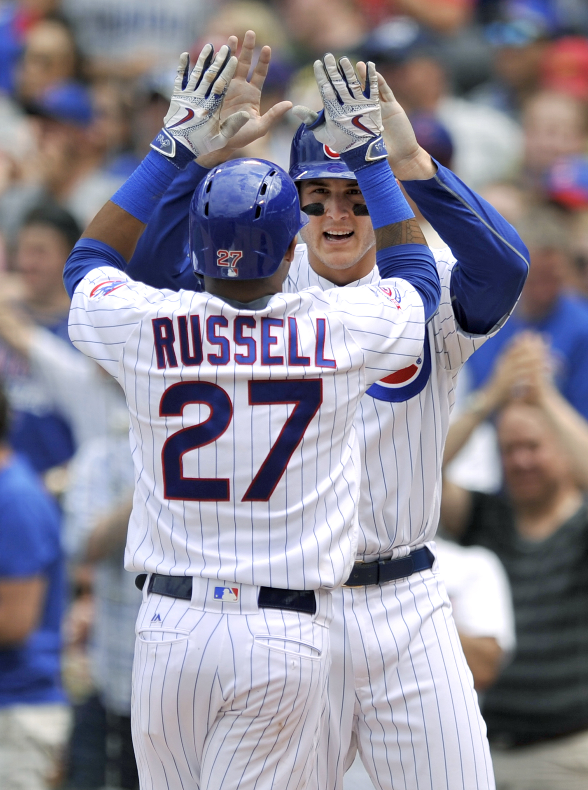 Chicago Cubs' Anthony Rizzo, back, celebrates with teammate Addison Russell (27) after Russell hit a two-run home run during the third inning of a baseball game against the Cincinnati Reds on Tuesday, July 5, 2016, in Chicago. (AP Photo/Paul Beaty)