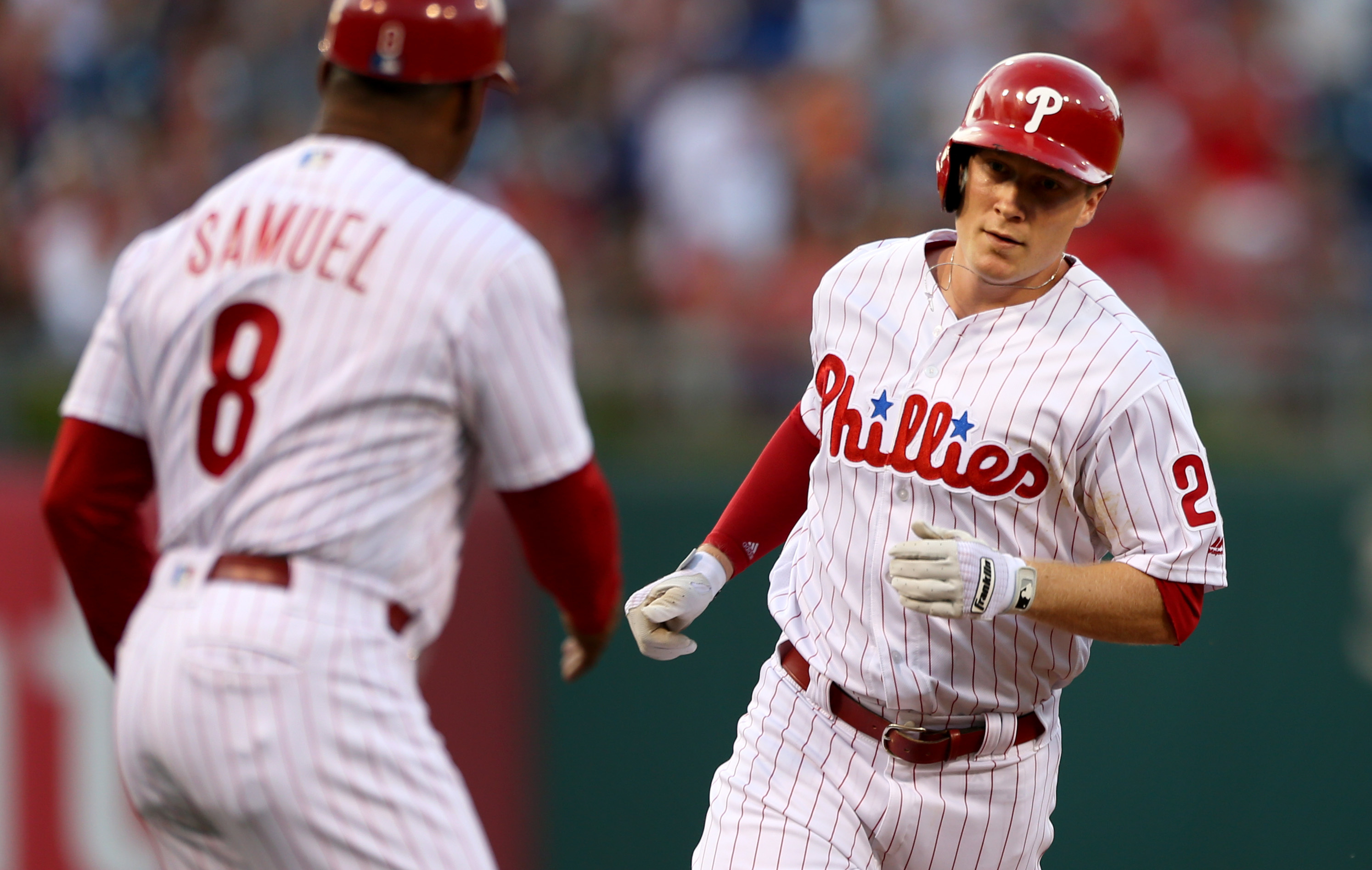 Philadelphia Phillies' Cody Asche is congratulated by third base coach Juan Samuel (8) after hitting a home run off Atlanta Braves starting pitcher Mike Foltynewicz during the fourth inning of a baseball game, Tuesday, July 5, 2016, in Philadelphia. (AP P