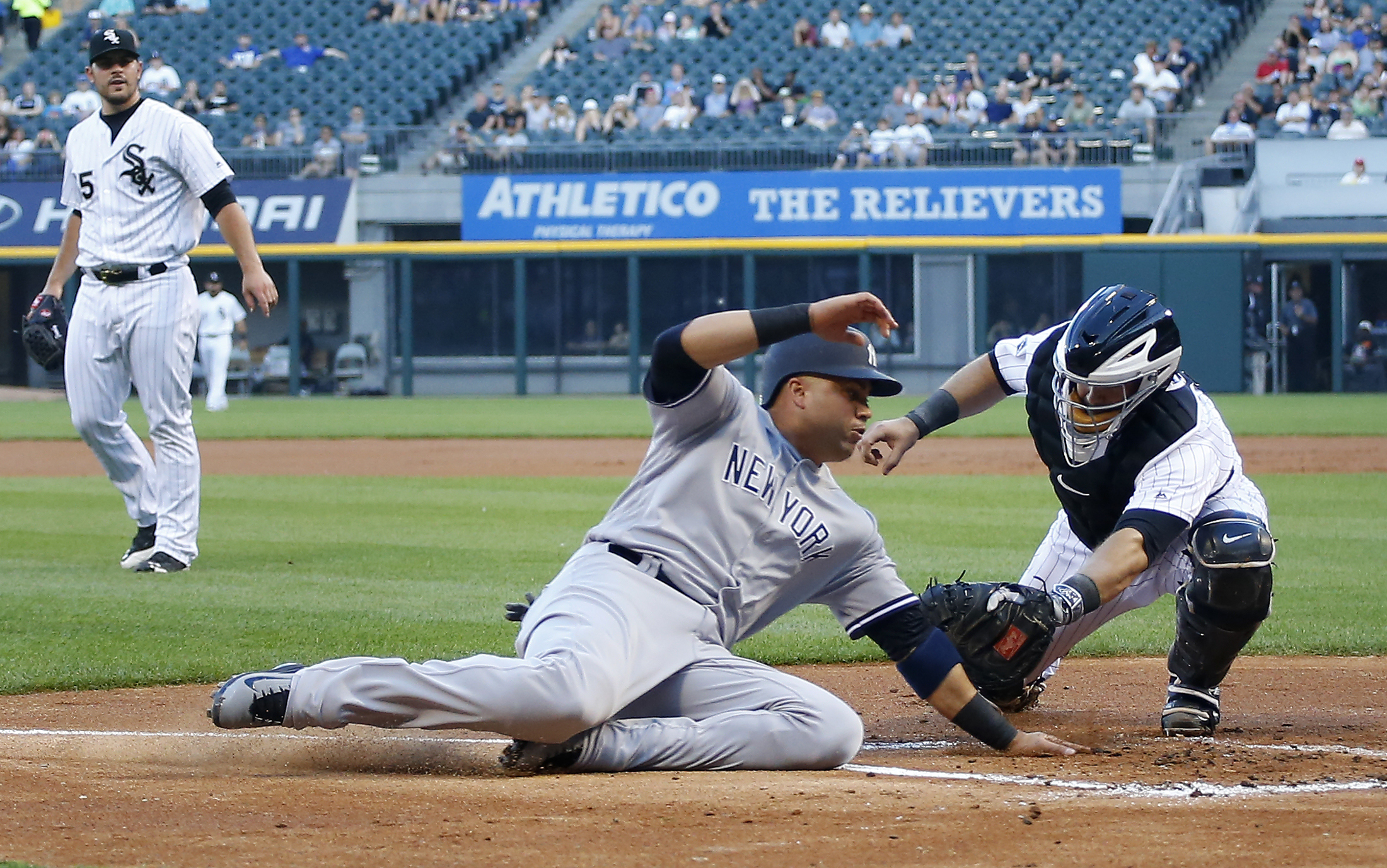 New York Yankees right fielder Carlos Beltran, center, is tagged out at home by Chicago White Sox catcher Alex Avila, right, as White Sox starting pitcher Carlos Rodon, left, looks on during the first inning of a baseball game in Chicago, on Tuesday, July