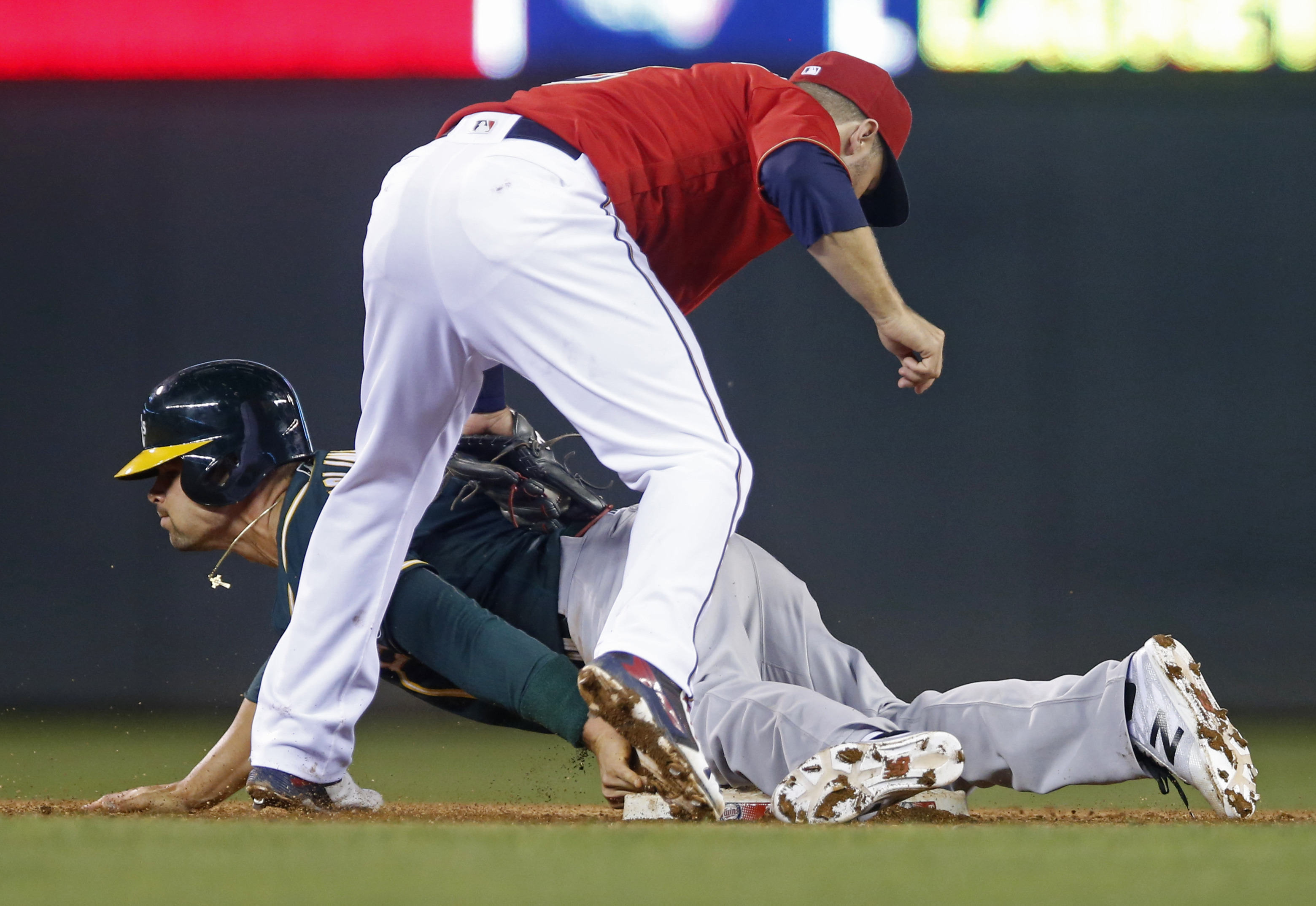 Oakland Athletics' Jake Smolinski, left, beats the tag by Minnesota Twins second baseman Brian Dozier as he steals second base in the fifth inning of a baseball game Tuesday, July 5, 2016, in Minneapolis. (AP Photo/Jim Mone)