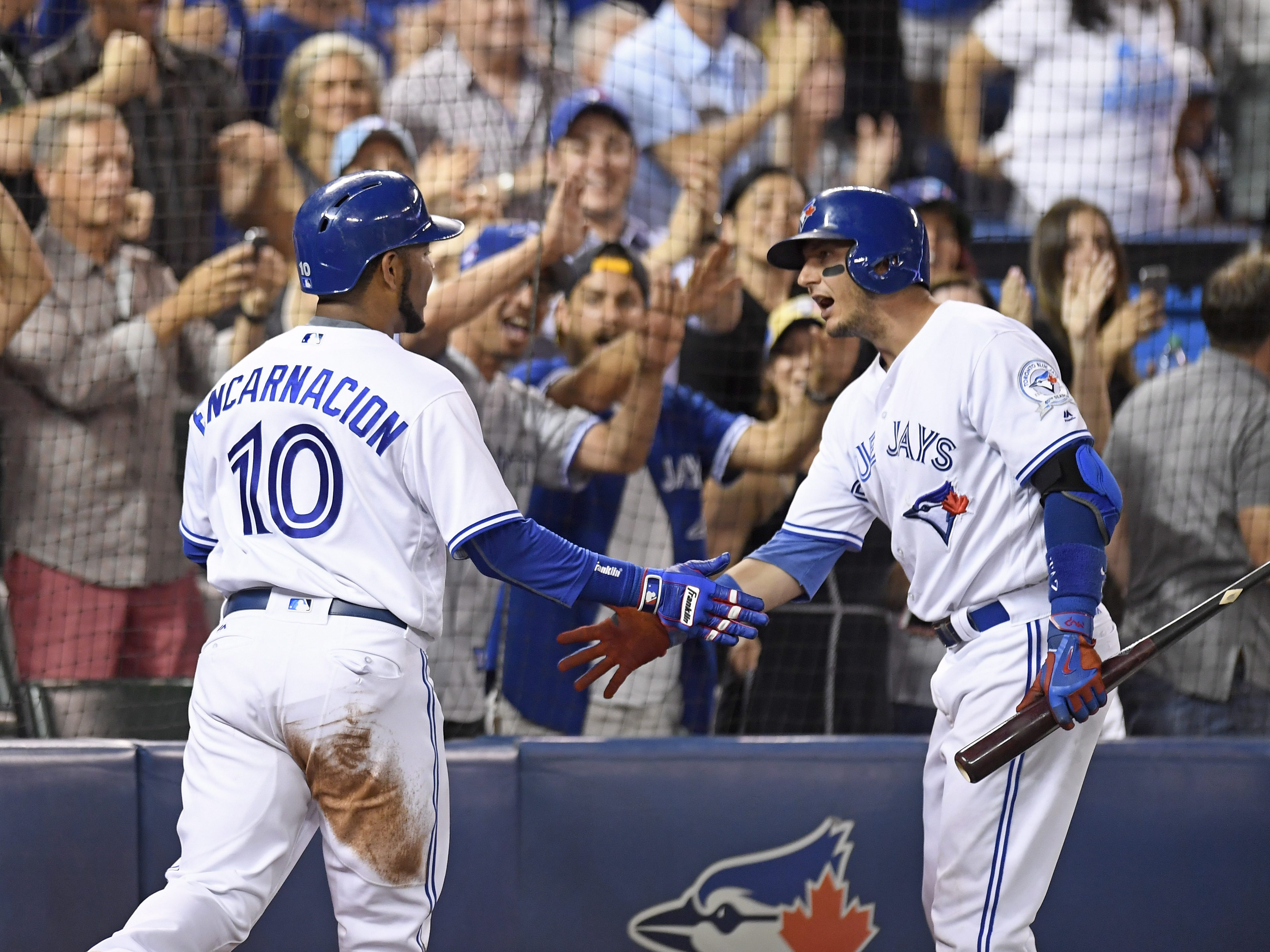 Toronto Blue Jays' Troy Tulowitzki, right, congratulates Edwin Encarnacion, who scored on a Michael Saunders single against the Kansas City Royals during the eighth inning of a baseball game Wednesday, July 6, 2016, in Toronto. (Frank Gunn/The Canadian Pr