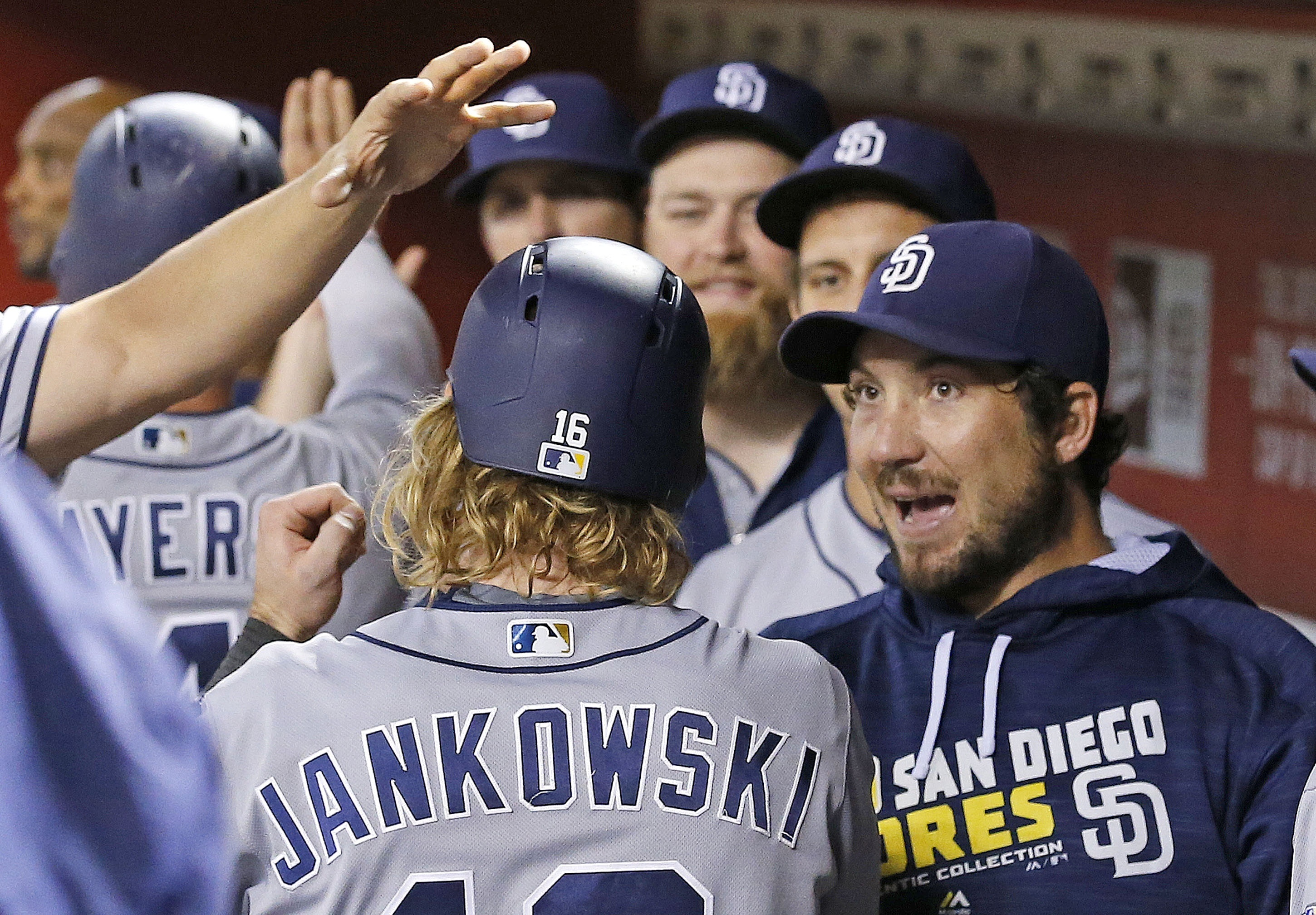 San Diego Padres' Travis Jankowski, left, celebrates his run scored against the Arizona Diamondbacks with teammates, including Brett Wallace, right, during the seventh inning of a baseball game Wednesday, July 6, 2016, in Phoenix. (AP Photo/Ross D. Frankl