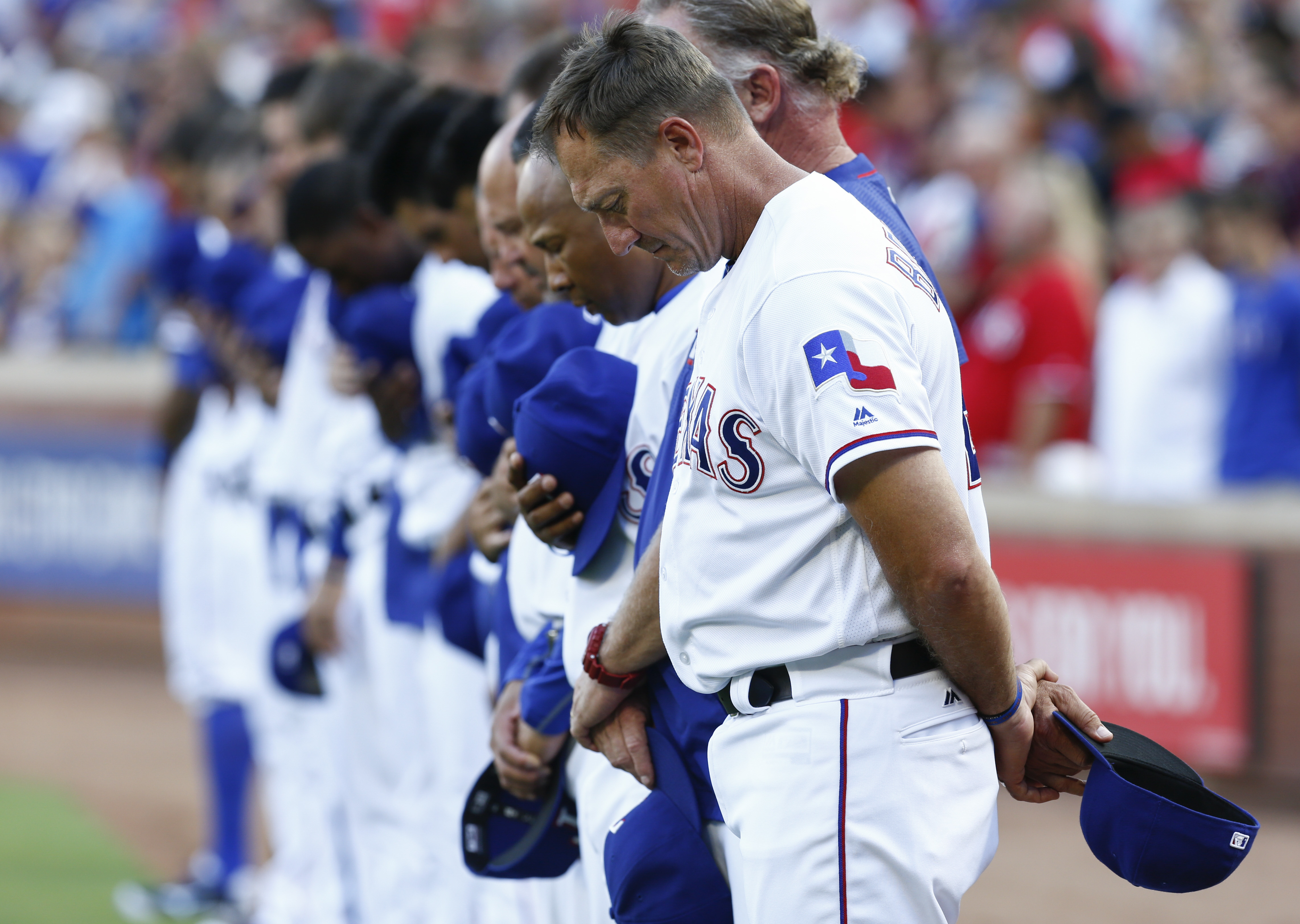 Members of the Texas Rangers including manager Jeff Banister observe a moment of silence, in remembrance of the people killed and injured in Dallas, before a baseball game against the Minnesota Twins at Globe Life Park, Friday, July 8, 2016, in Arlington,