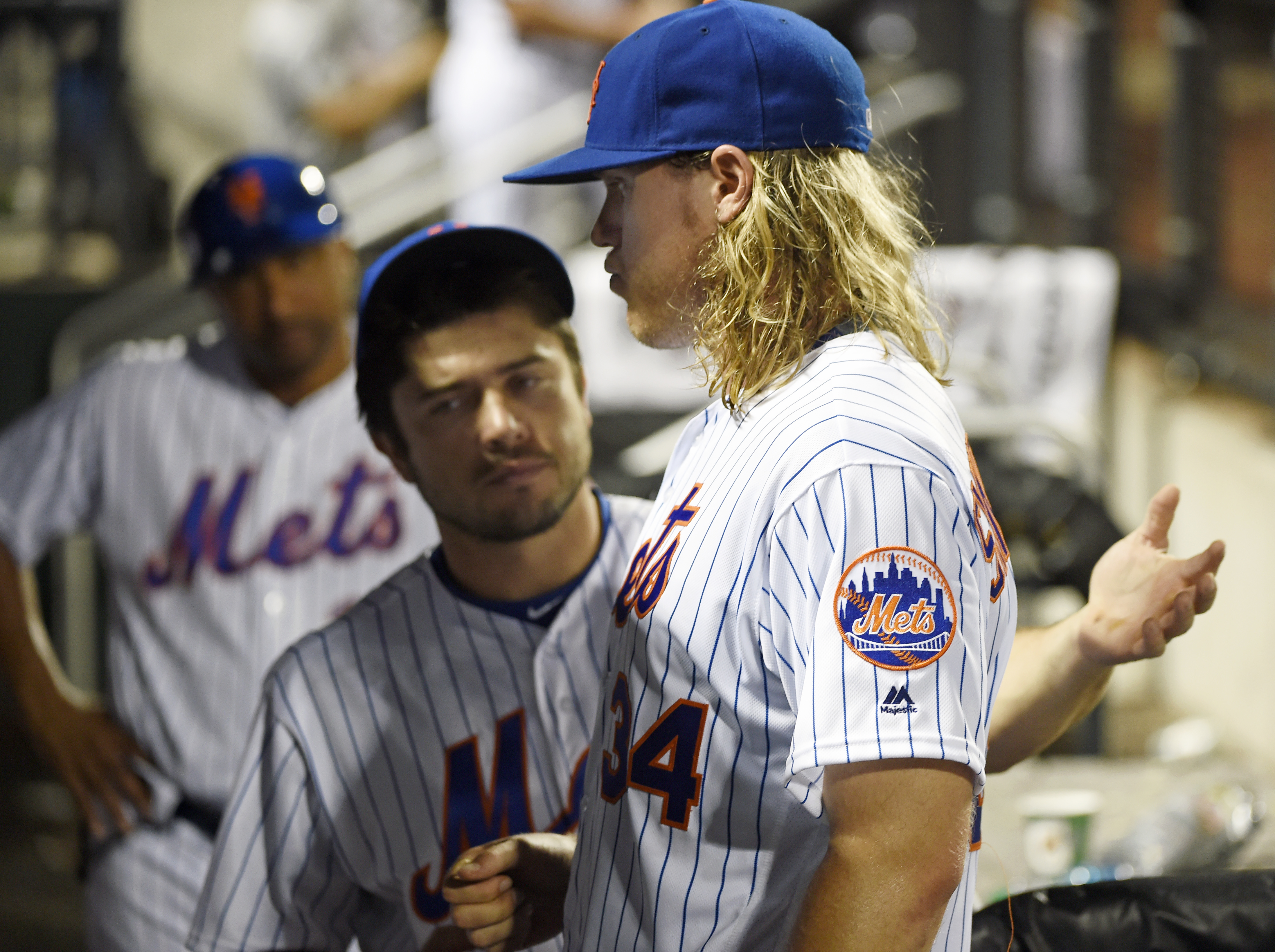 New York Mets catcher Travis d'Arnaud, center, talks with starting pitcher Noah Syndergaard (34) in the dugout after he was taken out of the game by manager Terry Collins in the fifth inning of a baseball game, Friday, July 8, 2016, in New York. A trainer