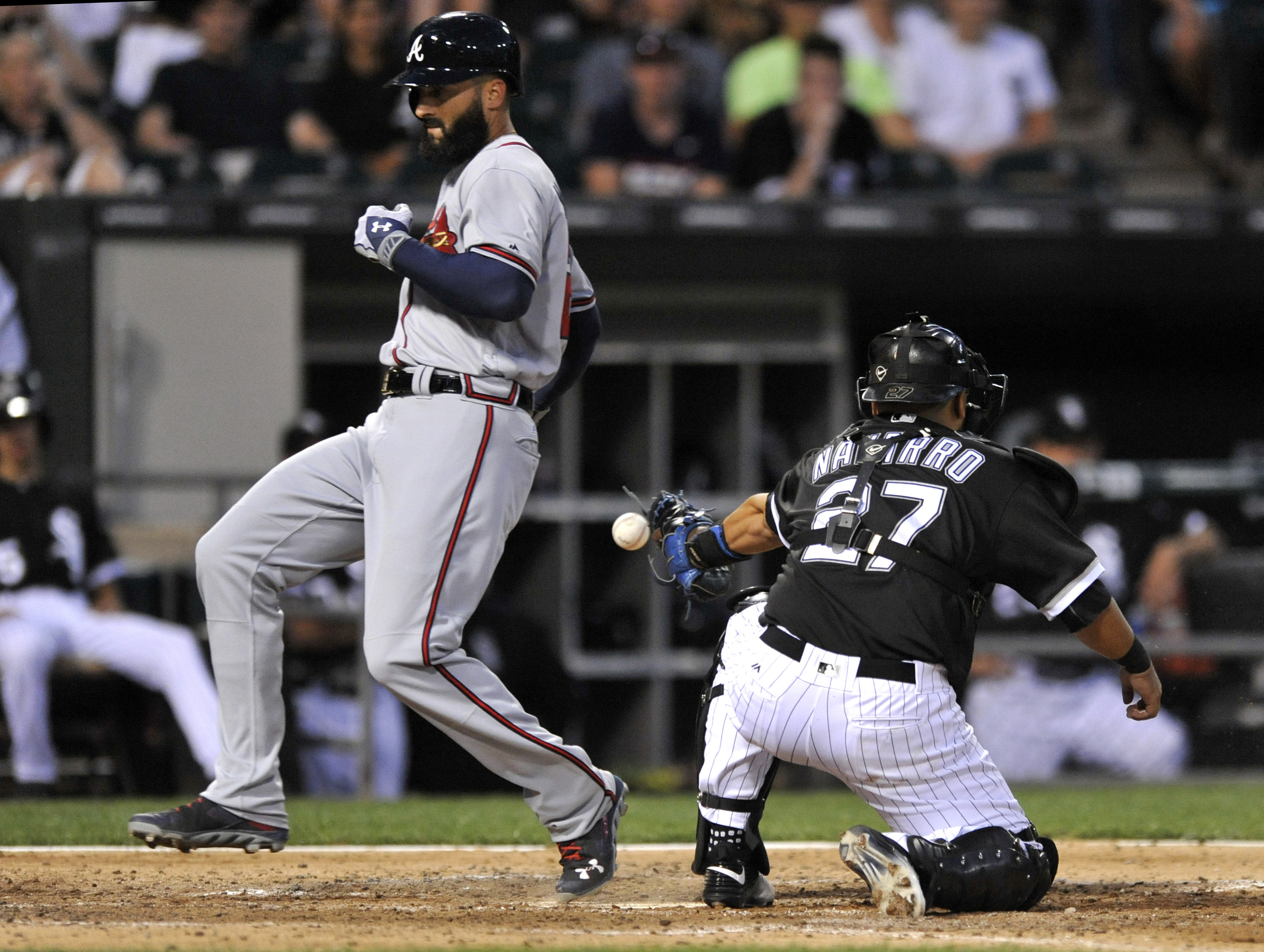 Atlanta Braves' Nick Markakis left, scores on a Jeff Francoeur double while Chicago White Sox catcher Dioner Navarro (27) misses the throw during the fifth inning of a interleague baseball game Friday, July 8, 2016, in Chicago. (AP Photo/Paul Beaty)