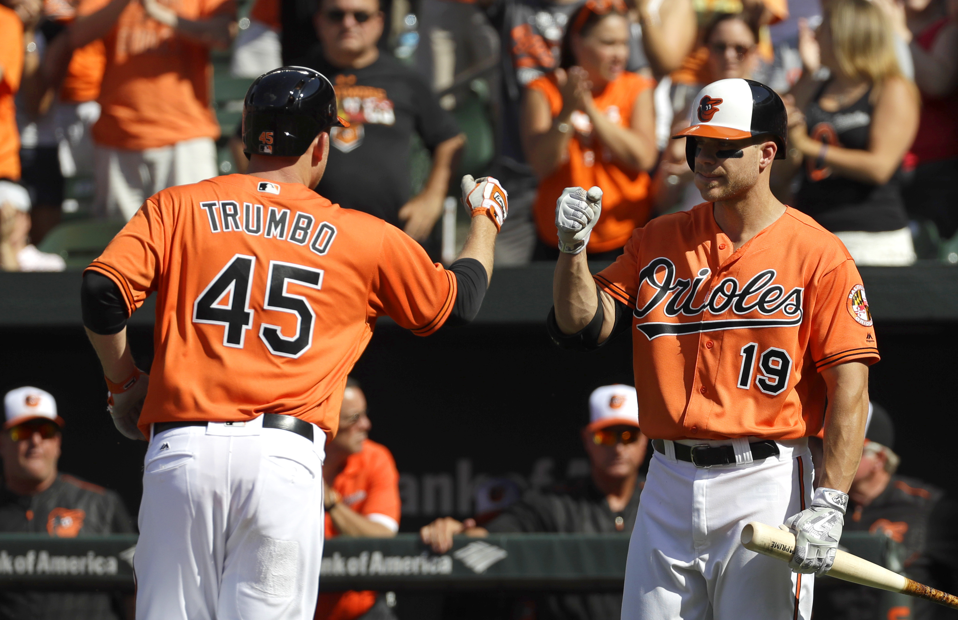 Baltimore Orioles' Mark Trumbo (45) fist-bumps teammate Chris Davis after hitting a solo home run in the second inning of a baseball game against the Los Angeles Angels in Baltimore, Saturday, July 9, 2016. (AP Photo/Patrick Semansky)