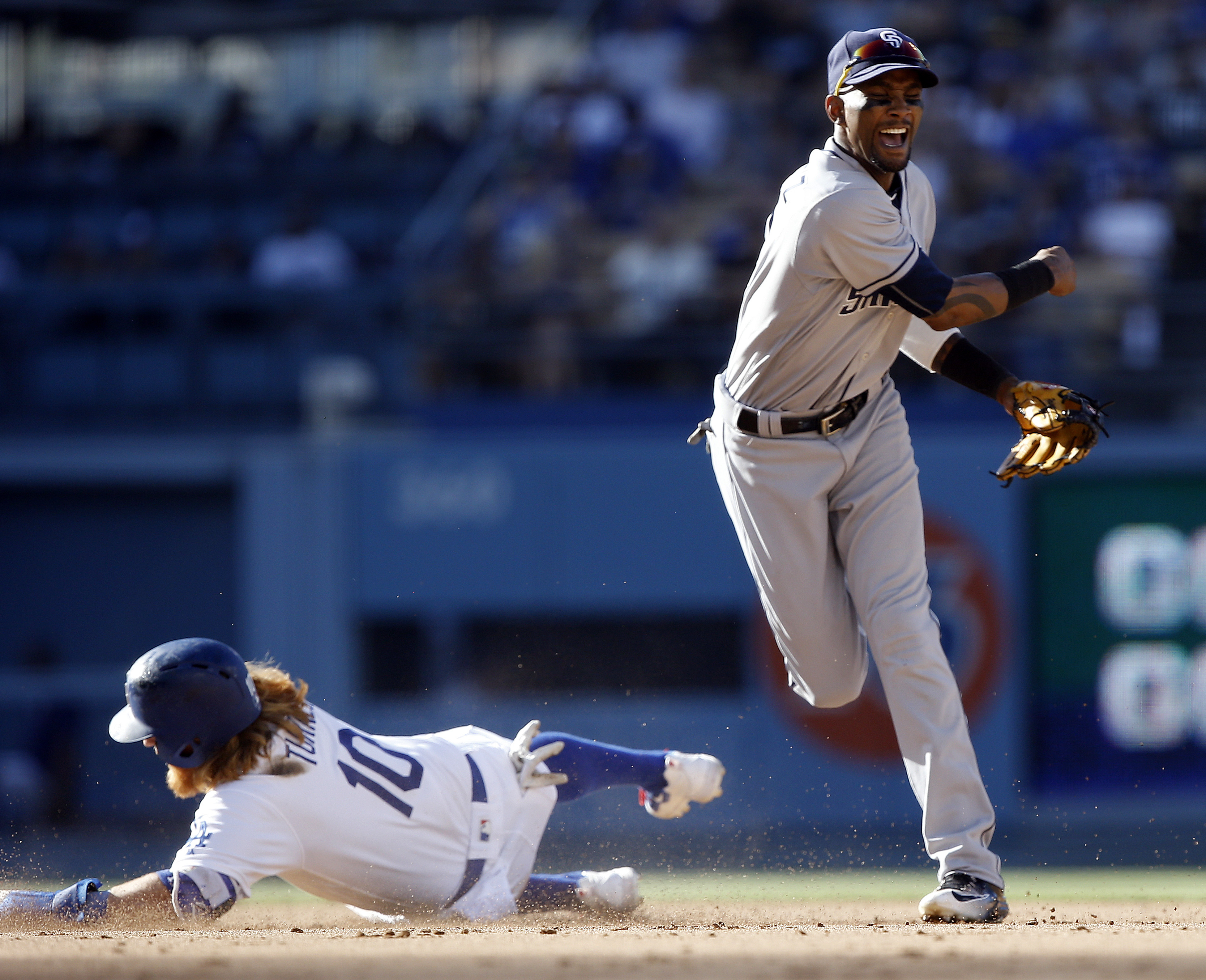 San Diego Padres shortstop Alexei Ramirez, right, watches his throw to first after forcing out Los Angeles Dodgers' Justin Turner, left, during the fifth inning of a baseball game in Los Angeles, Saturday, July 9, 2016. Corey Seager scored, and Adrian Gon