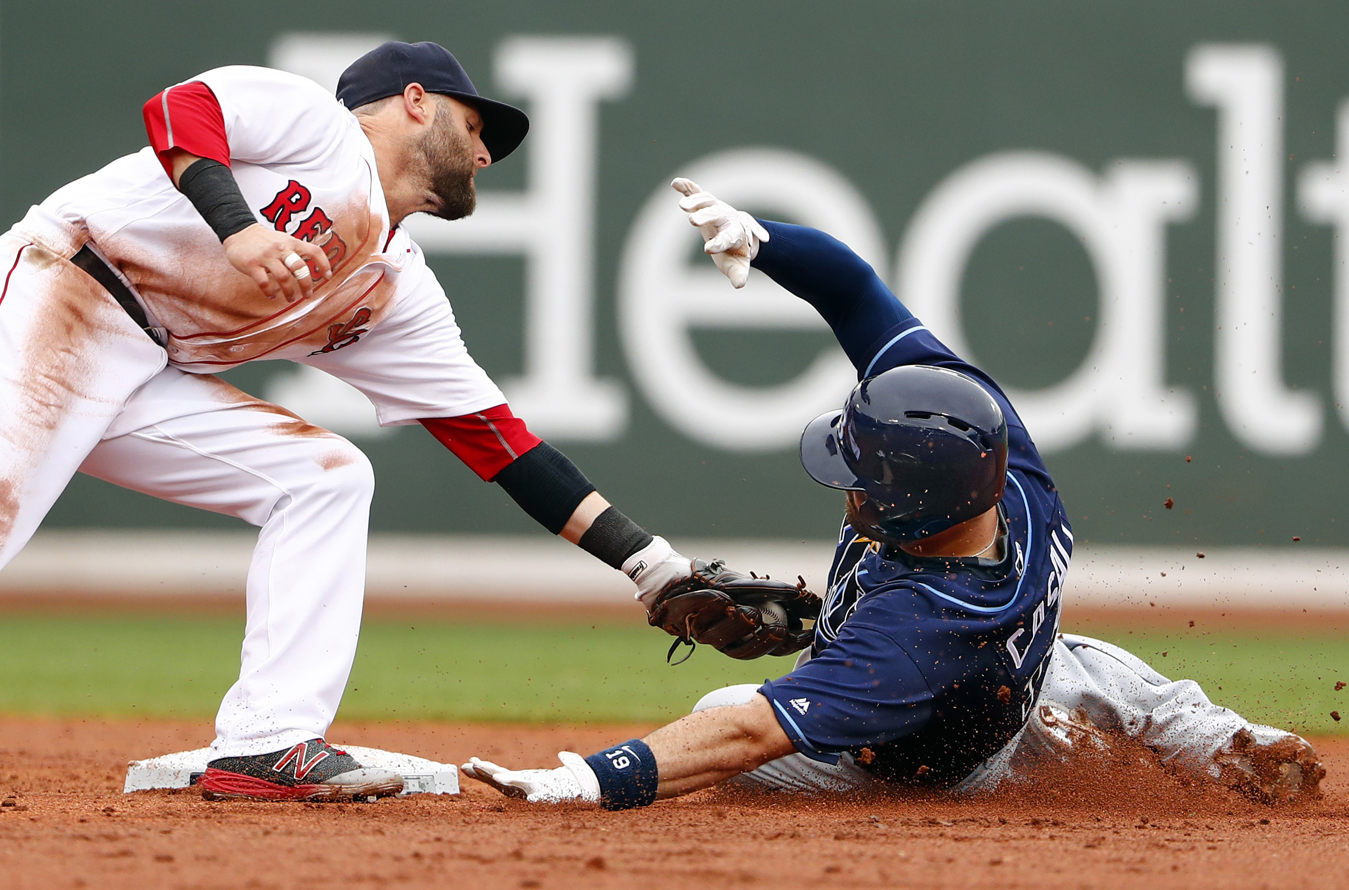 Boston Red Sox second baseman Dustin Pedroia tags out Tampa Bay Rays' Curt Casali at second trying to stretch a single into a double during the second inning of a baseball game at Fenway Park in Boston Sunday, July 10, 2016. (AP Photo/Winslow Townson)