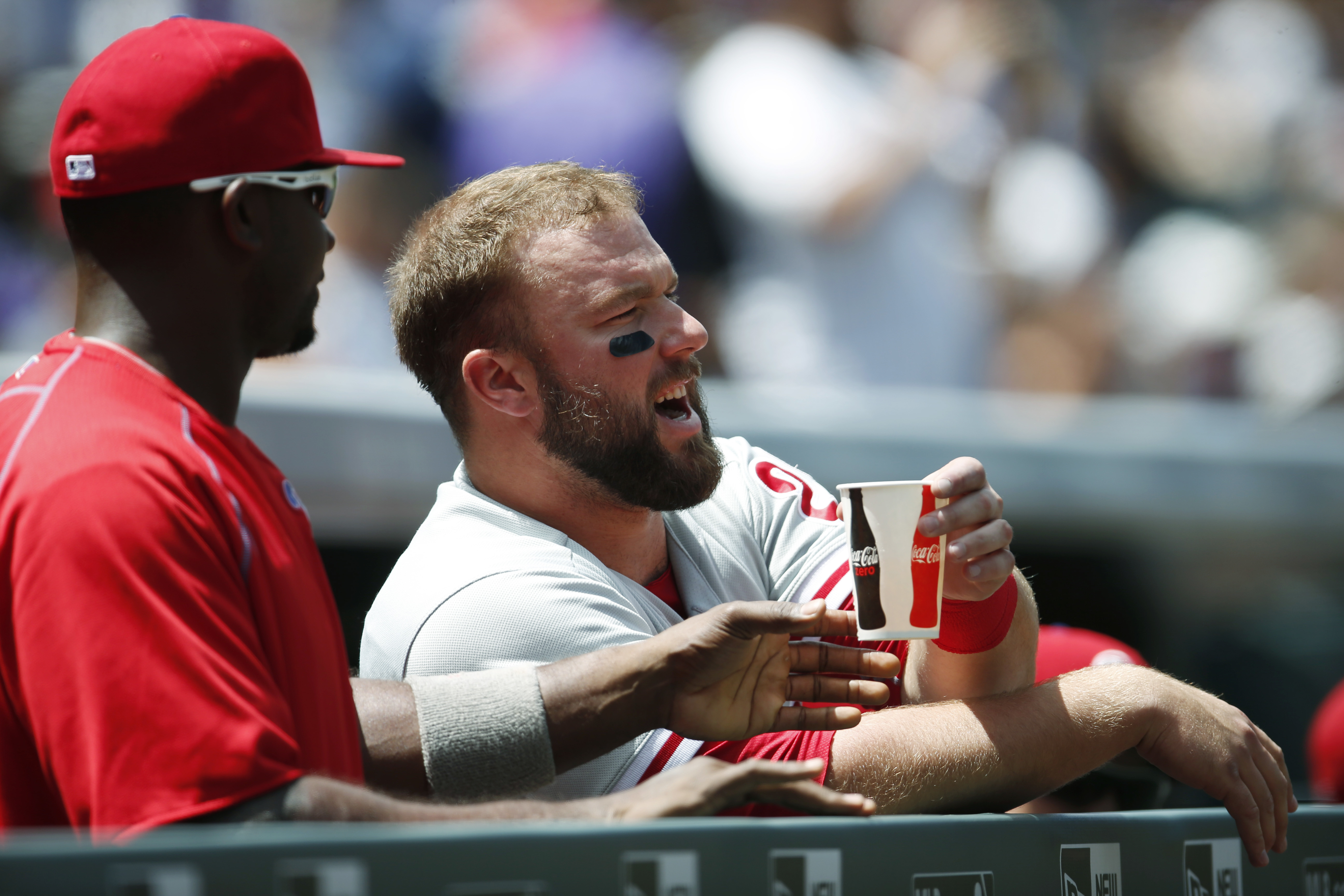 Philadelphia Phillies first baseman Ryan Howard, left, shares a cup of water with catcher Cameron Rupp as they look on against the Colorado Rockies in the first inning of a baseball game Sunday, July 10, 2016, in Denver. High temperatures were in the mid-