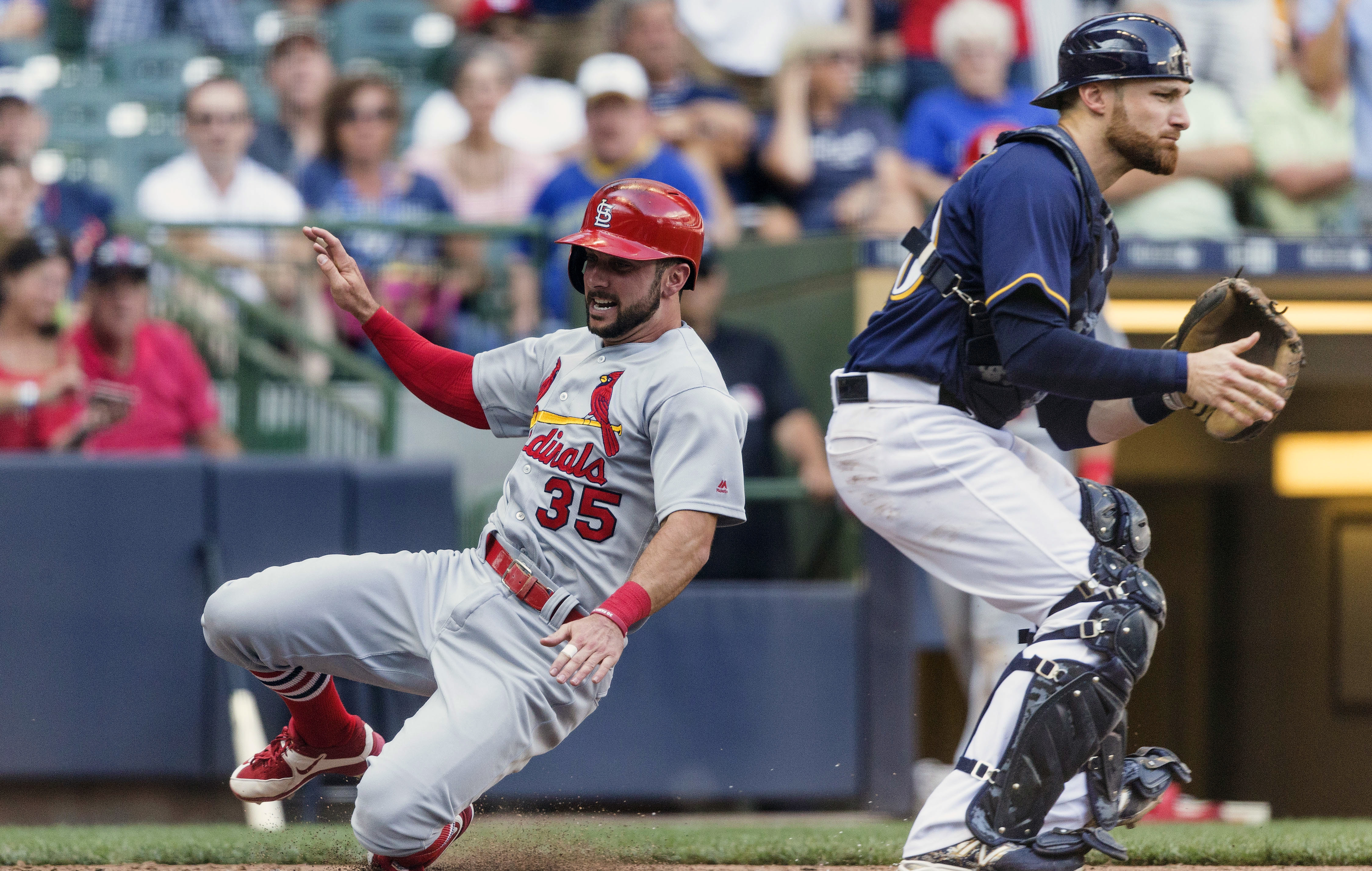 Milwaukee Brewers' Jonathan Lucroy, right, waits for the throw as St. Louis Cardinals' Greg Garcia scores from first on Matt Adams' double during the ninth inning of a baseball game Sunday, July 10, 2016, in Milwaukee. (AP Photo/Tom Lynn)