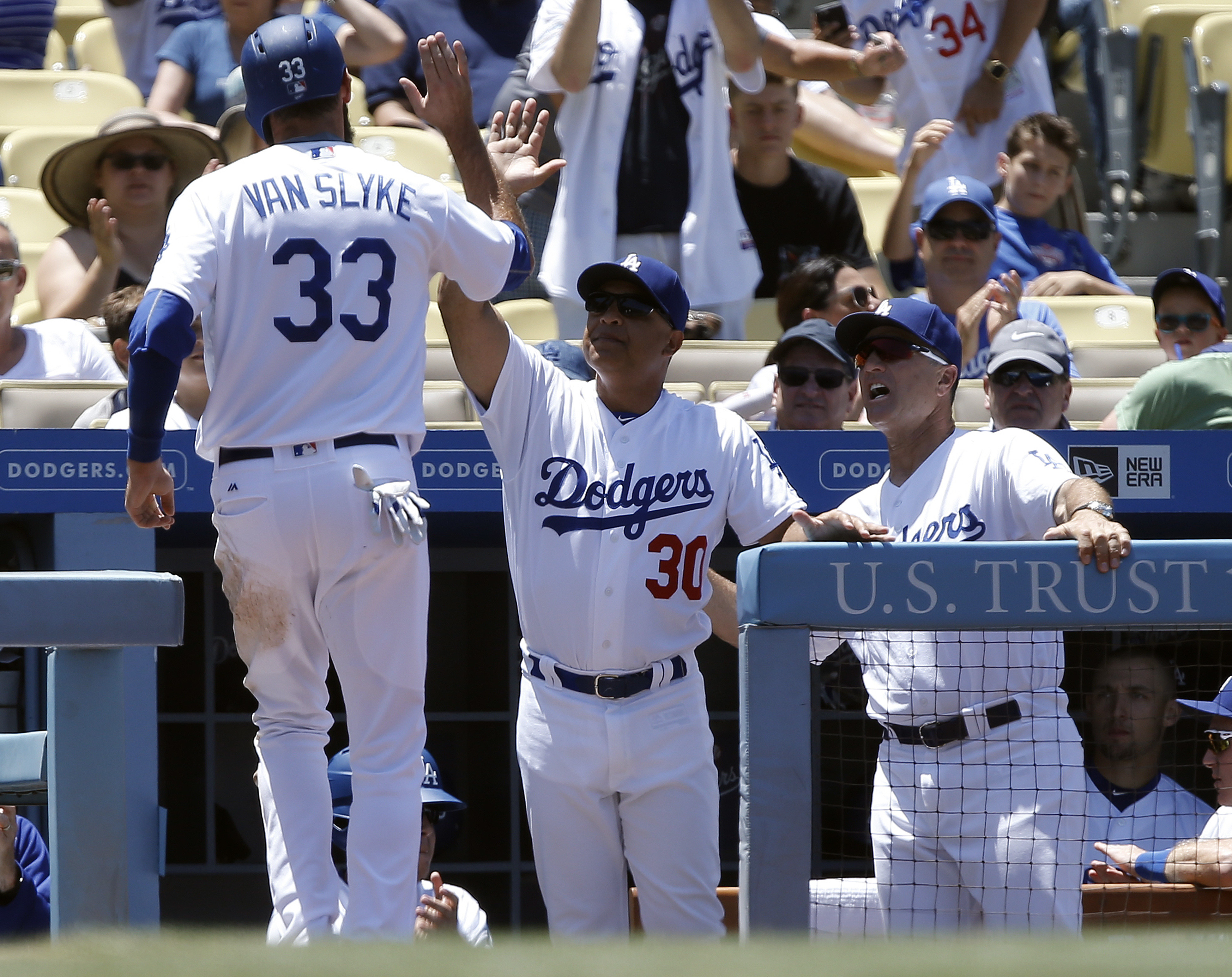 Los Angeles Dodgers' Scott Van Slyke, left, is congratulated by manager Dave Roberts, center, and coach Bob Geren, right, after scoring on a single by Howie Kendrick against the San Diego Padres during the second inning of a baseball game in Los Angeles,