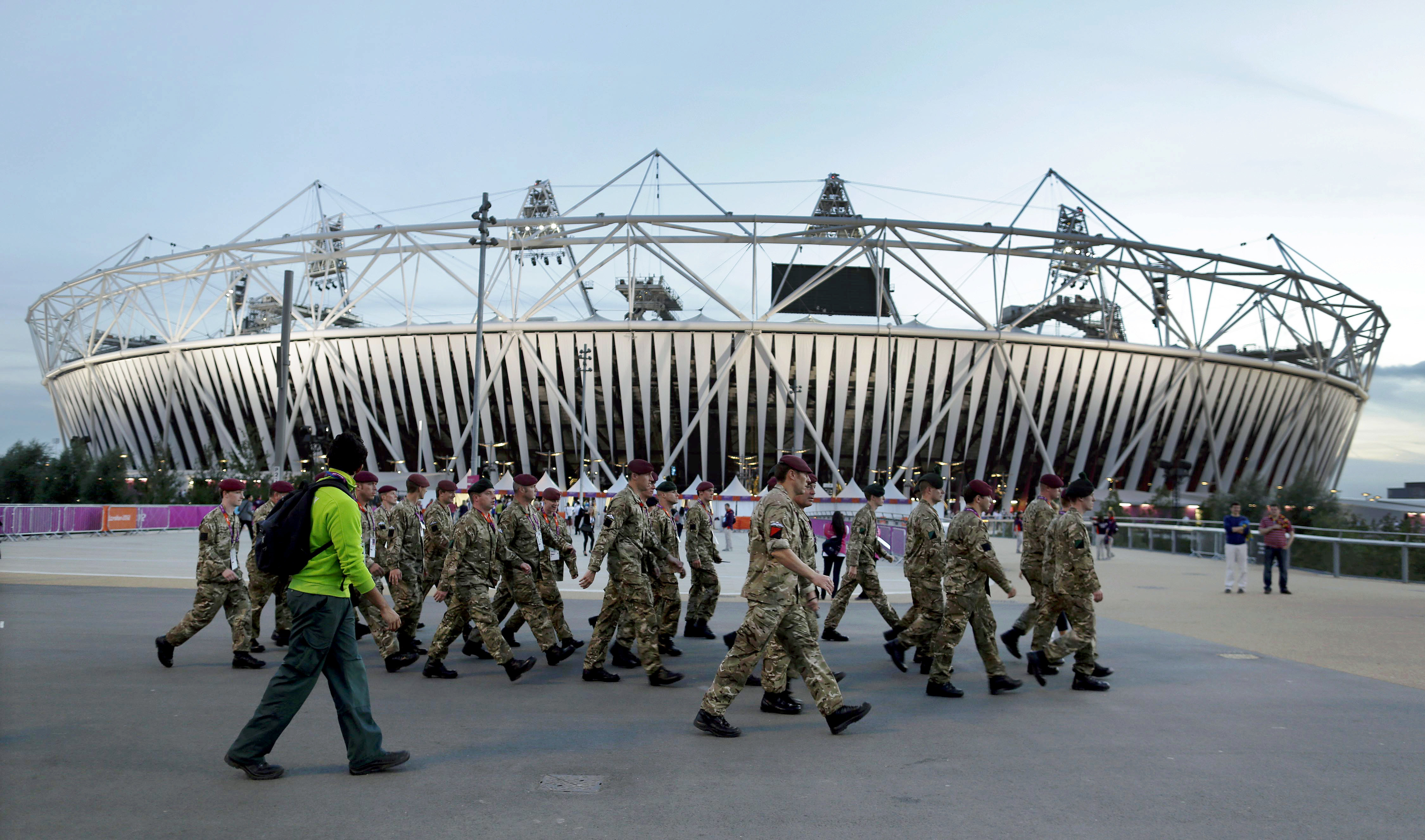 FILE- In this Aug. 12, 2012, file photo, ,embers of the British military march by Olympic Stadium before the Closing Ceremony of the 2012 Summer Olympics in London. The players' association says Major League Baseball has given up plans to play regular-sea