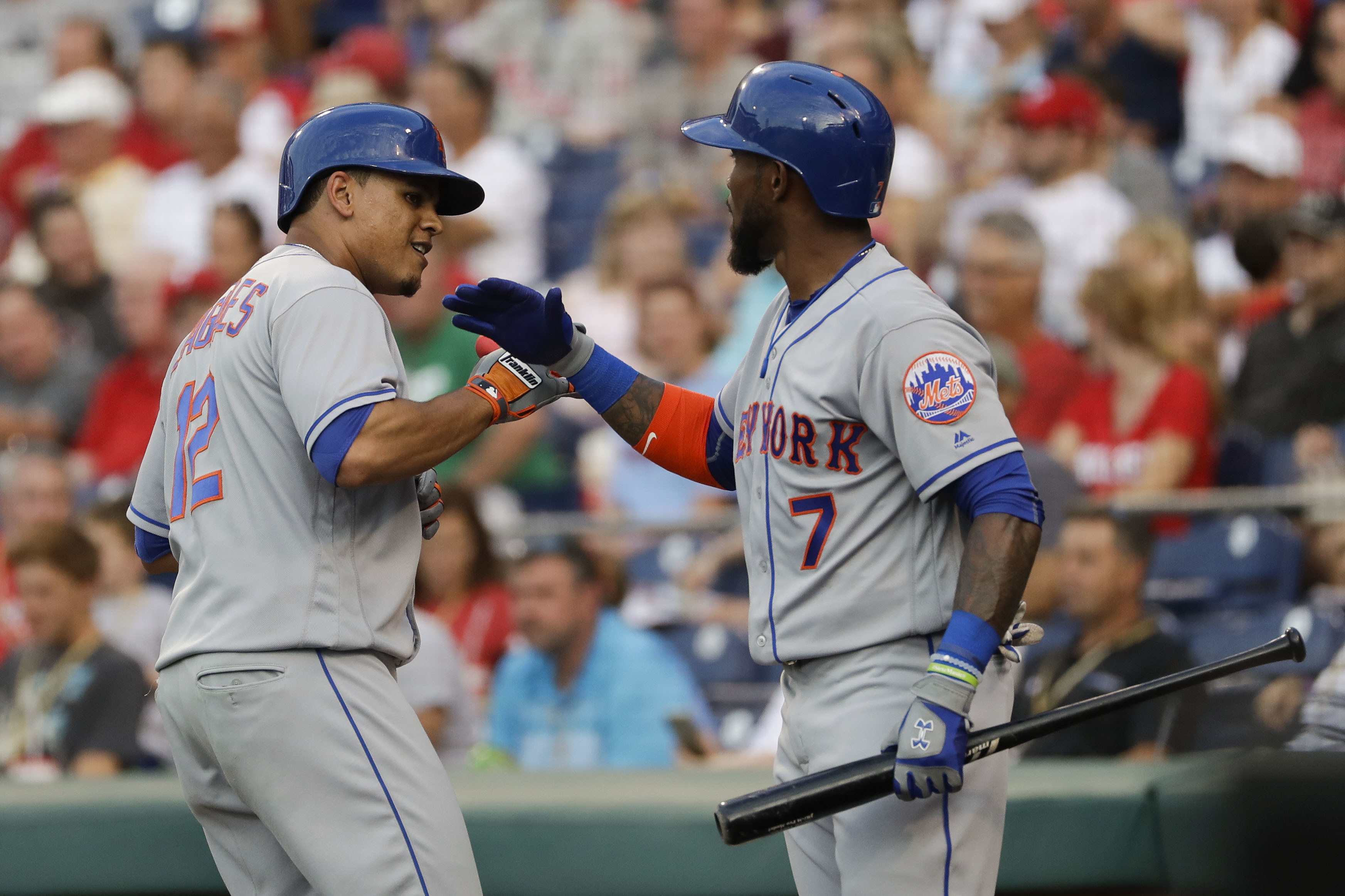 New York Mets' Juan Lagares, left, and Jose Reyes celebrate after Lagares' home run off Philadelphia Phillies starting pitcher Jeremy Hellickson during the third inning of a baseball game, Friday, July 15, 2016, in Philadelphia. (AP Photo/Matt Slocum)