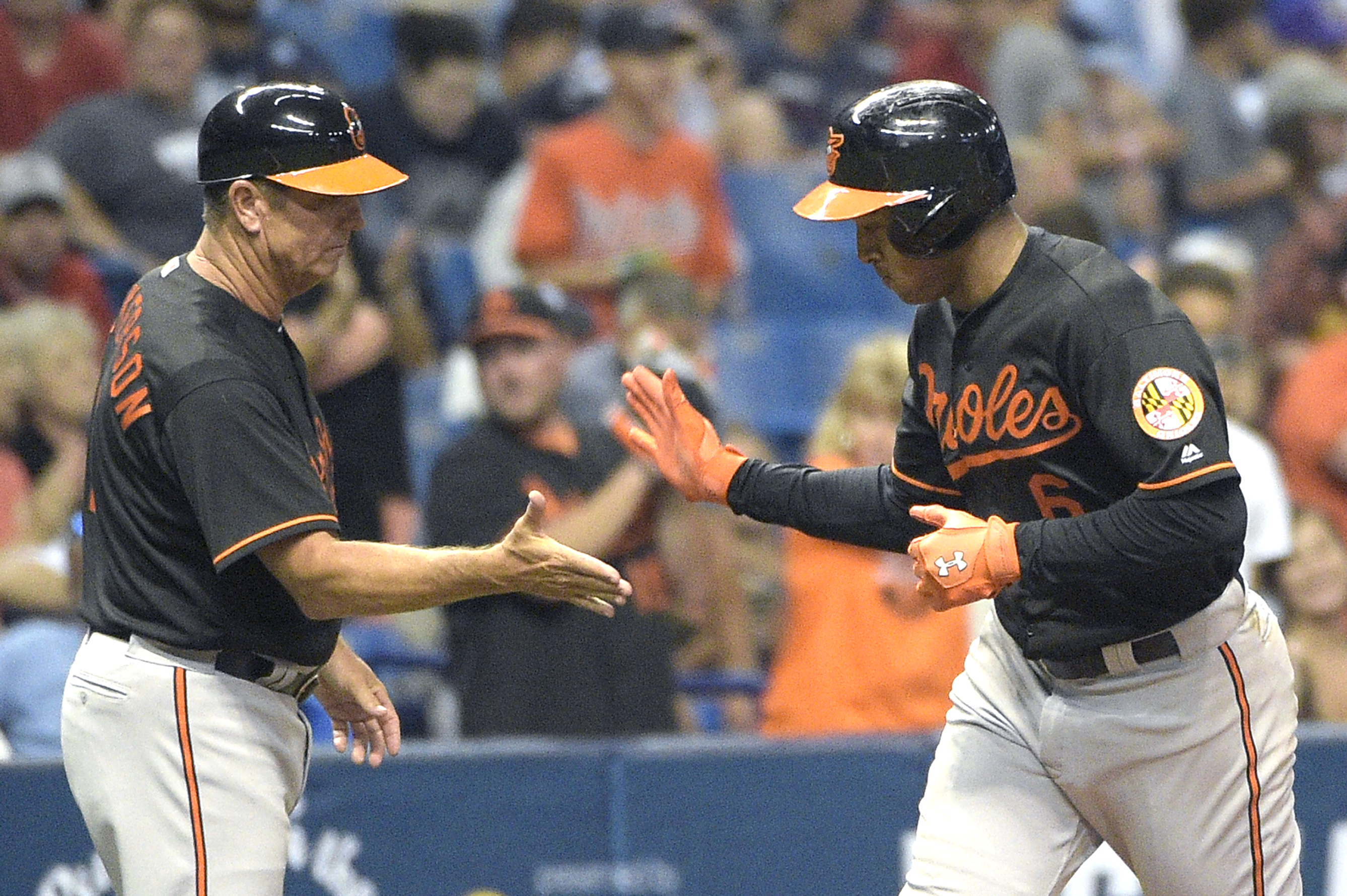 Baltimore Orioles' Jonathan Schoop (6) is congratulated by third base coach Bobby Dickerson while rounding the bag after hitting a solo home run during the eighth inning of a baseball game against the Tampa Bay Rays in St. Petersburg, Fla., Friday, July 1