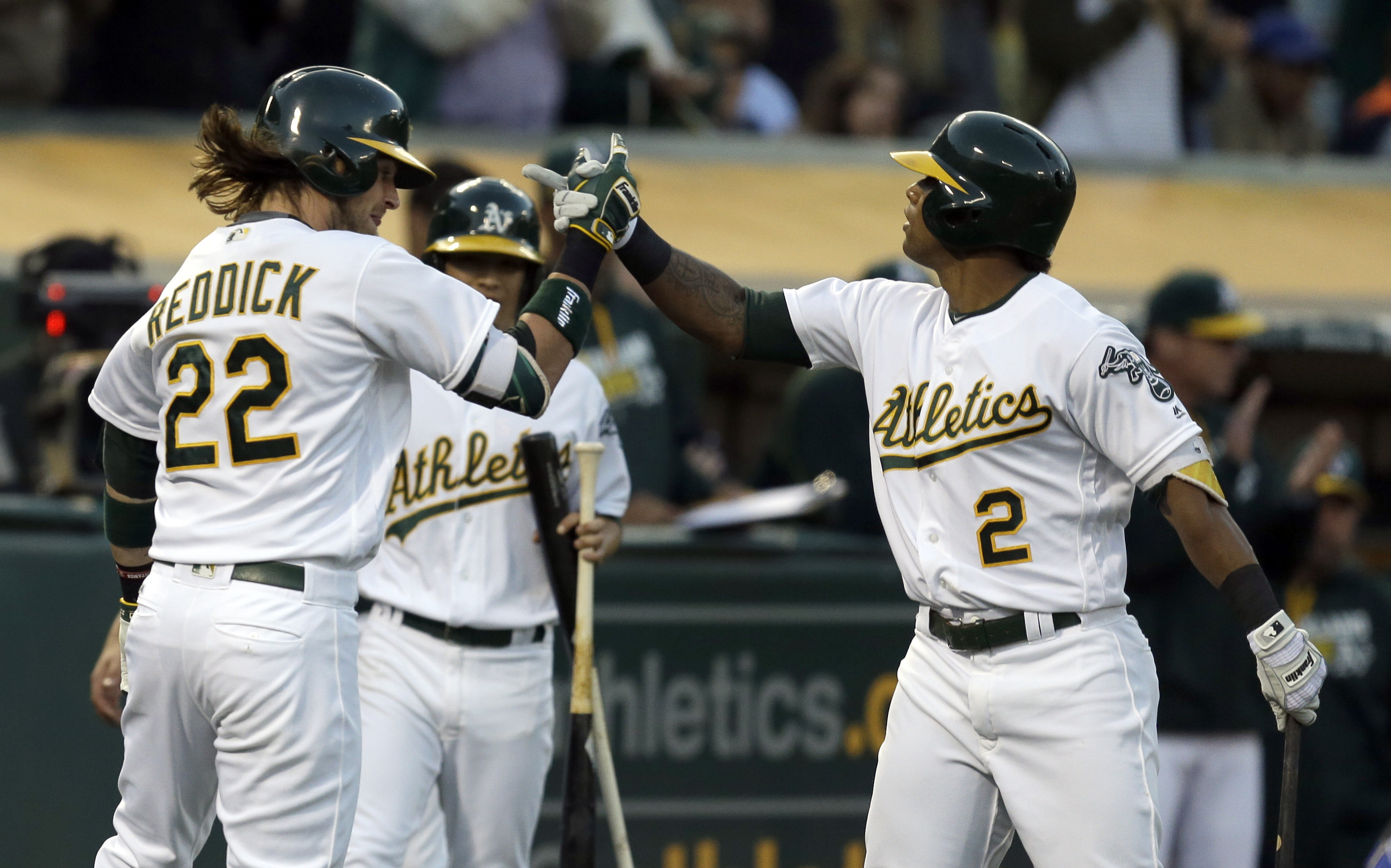 Oakland Athletics' Josh Reddick, left, and Khris Davis (2) celebrate after Reddick hit a two-run home run against the Toronto Blue Jays during the fifth inning of a baseball game Friday, July 15, 2016, in Oakland, Calif. (AP Photo/Ben Margot)