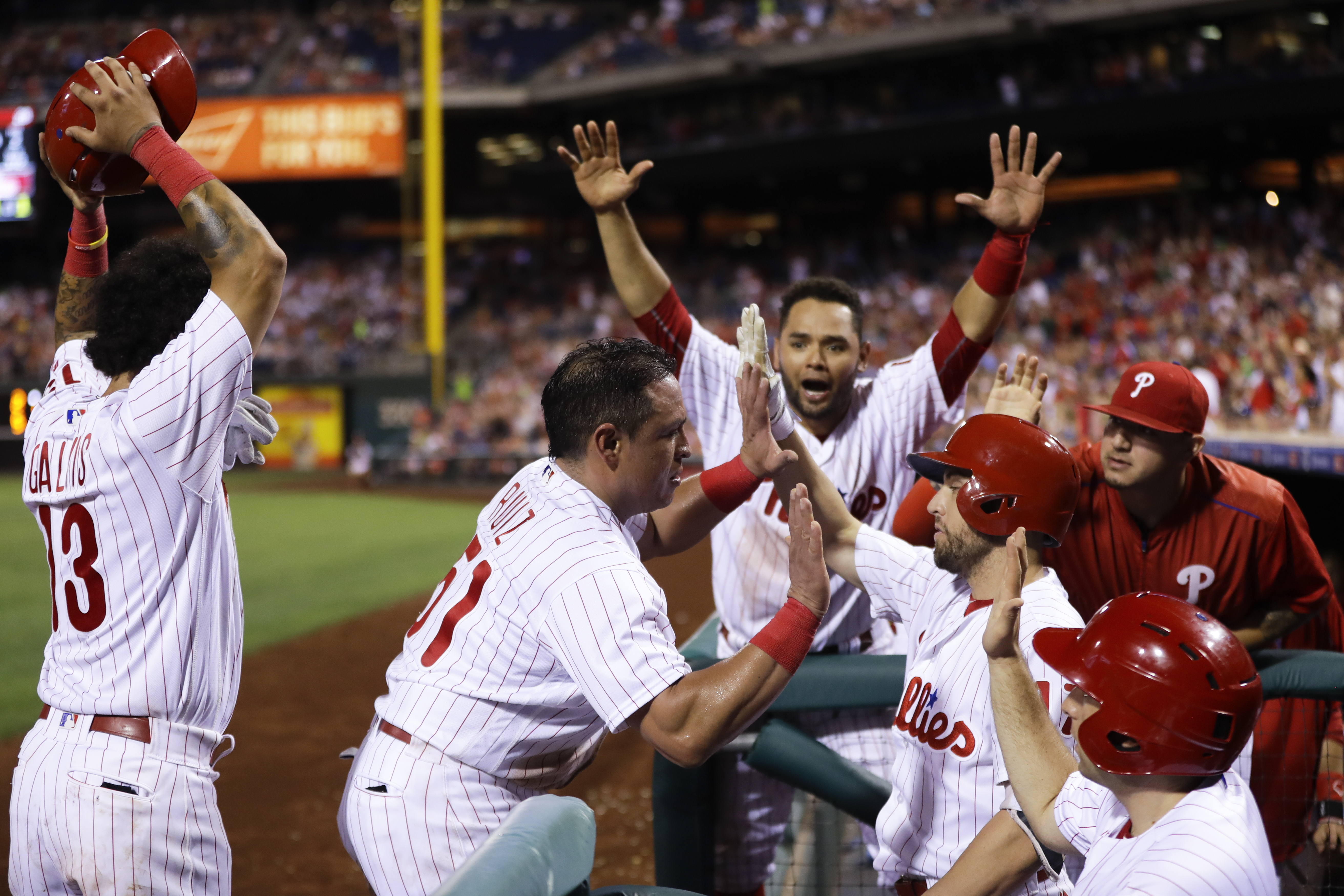 Philadelphia Phillies' Carlos Ruiz, center, celebrates with teammates after scoring on a wild pitch by New York Mets relief pitcher Erik Goeddel during the eighth inning of a baseball game, Saturday, July 16, 2016, in Philadelphia. Philadelphia won 4-2. (