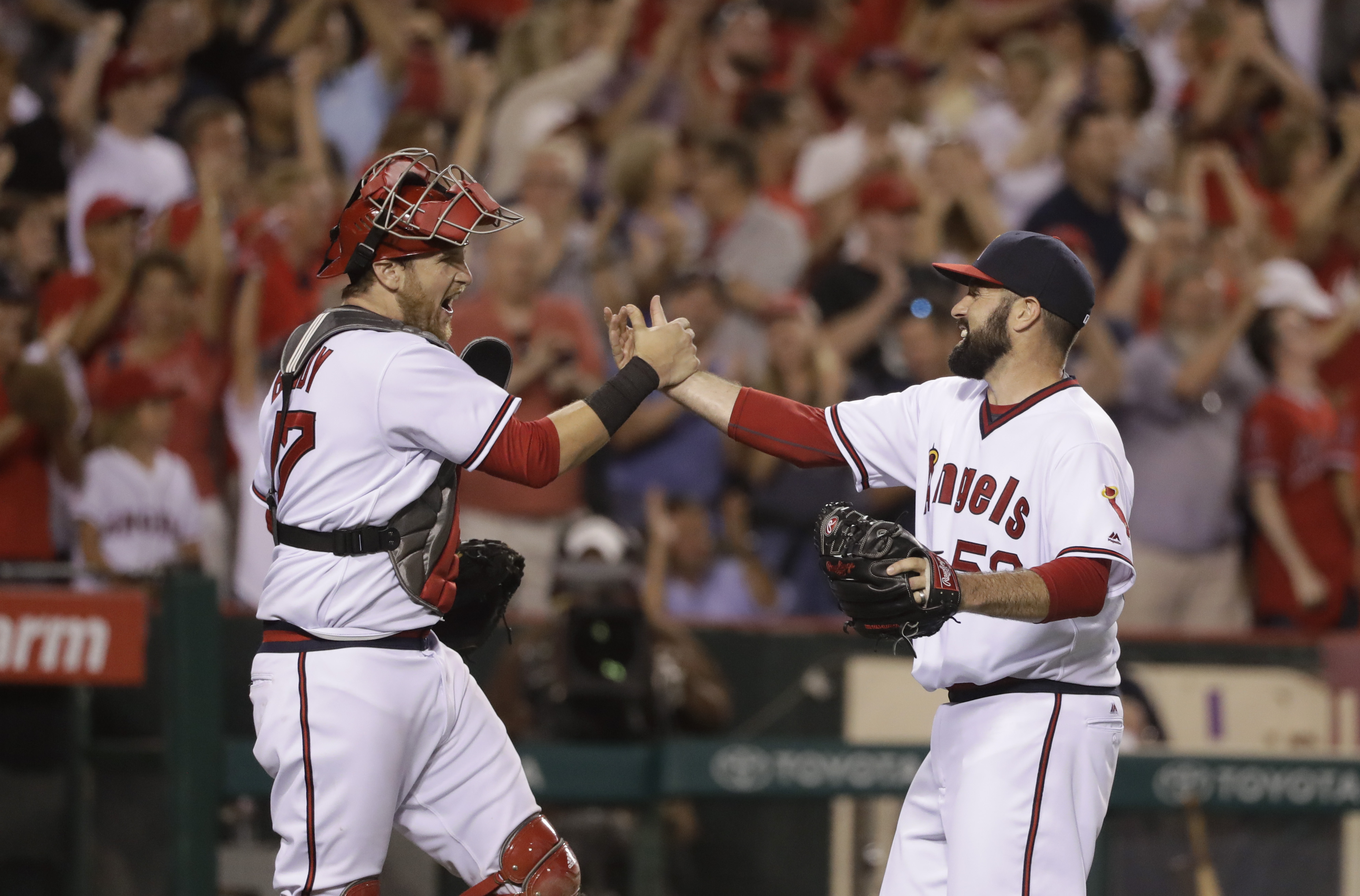 Los Angeles Angels starting pitcher Matt Shoemaker, right, and catcher Jett Bandy celebrate the team's 1-0 win against the Chicago White Sox in a baseball game, Saturday, July 16, 2016, in Anaheim, Calif. (AP Photo/Jae C. Hong)