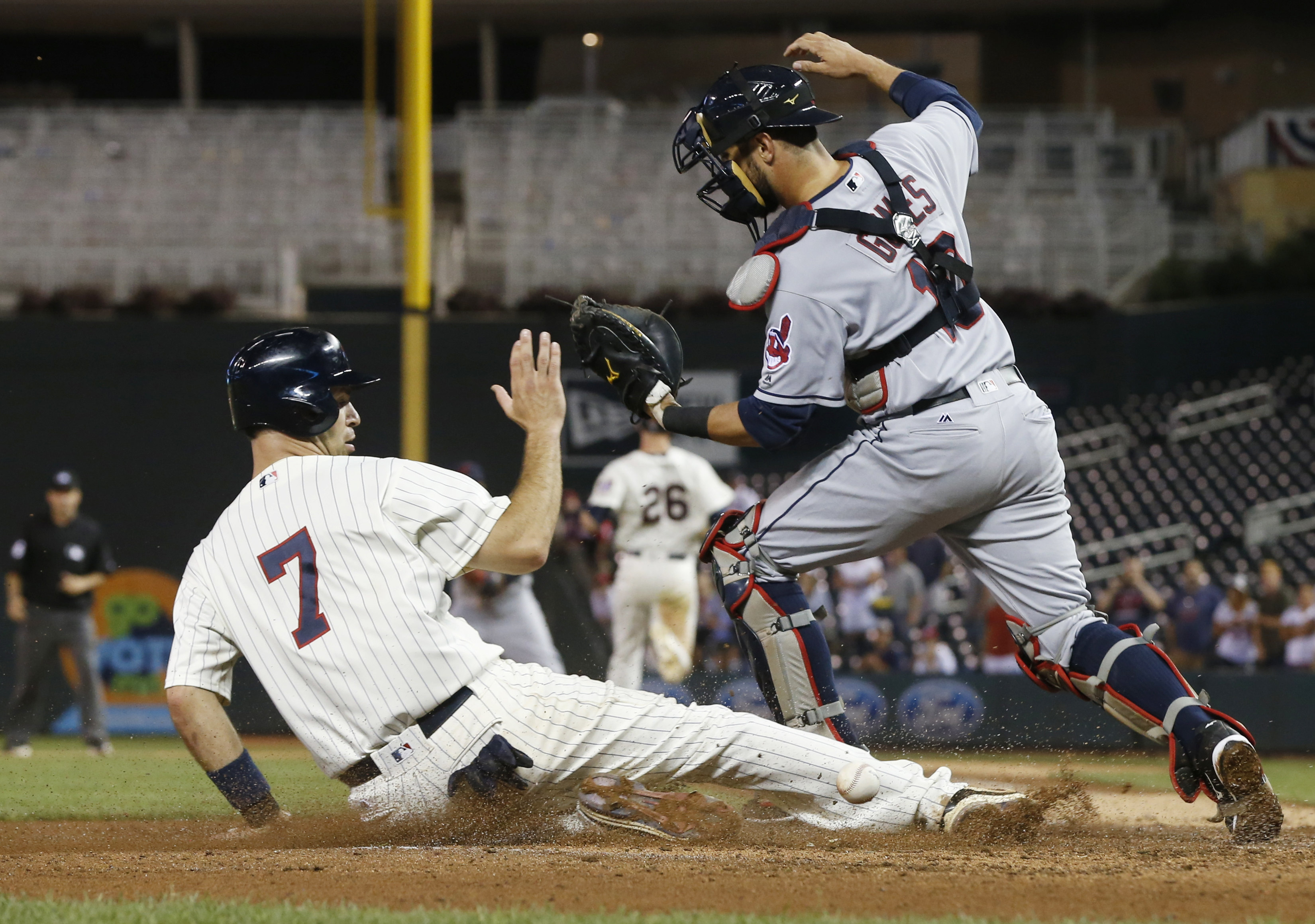 Minnesota Twins' Joe Mauer scores the go-ahead run as Cleveland Indians catcher Yan Gomes can't handle the throw to the plate on a fielder's choice with the bases loaded in the 11th inning of a baseball game Sunday, July 17, 2016, in Minneapolis. The Twin