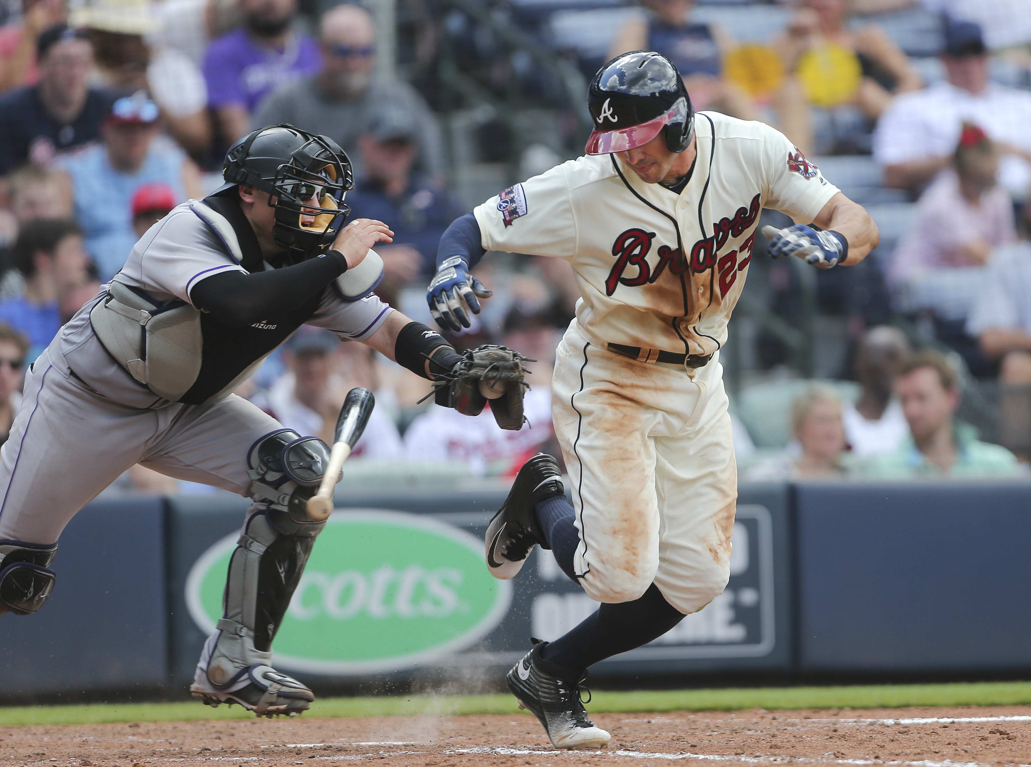Atlanta Braves' Chase d'Arnaud (23) is chased by Colorado Rockies catcher Tony Wolters (14) as he runs to first base after a dropped third strike in the seventh inning of a baseball game Sunday, July 17, 2016, in Atlanta. d'Arnaud was out at first. (AP Ph
